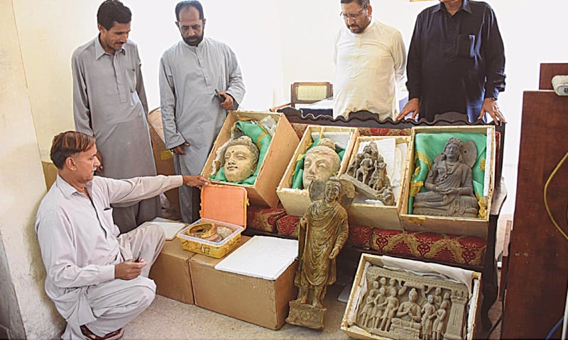 A Pakistani Customs staffer pictured with the seized artefacts on Friday. — Paper
