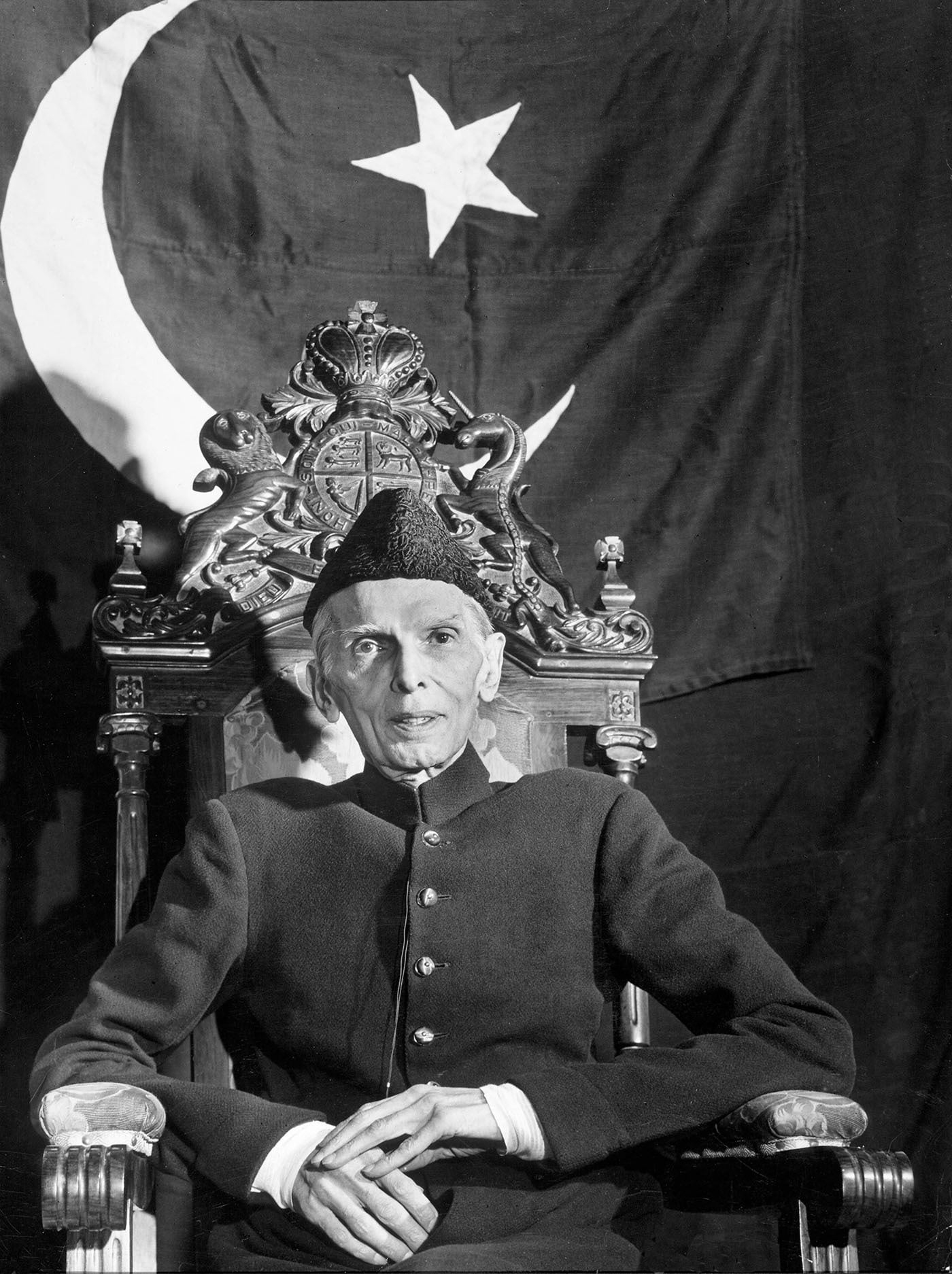 Quaid-i-Azam Mohammad Ali Jinnah is seated with the Pakistan flag draped behind him in Karachi in December 1947. — Excerpted with permission from Witness to Life and Freedom, Roli Books, Delhi
