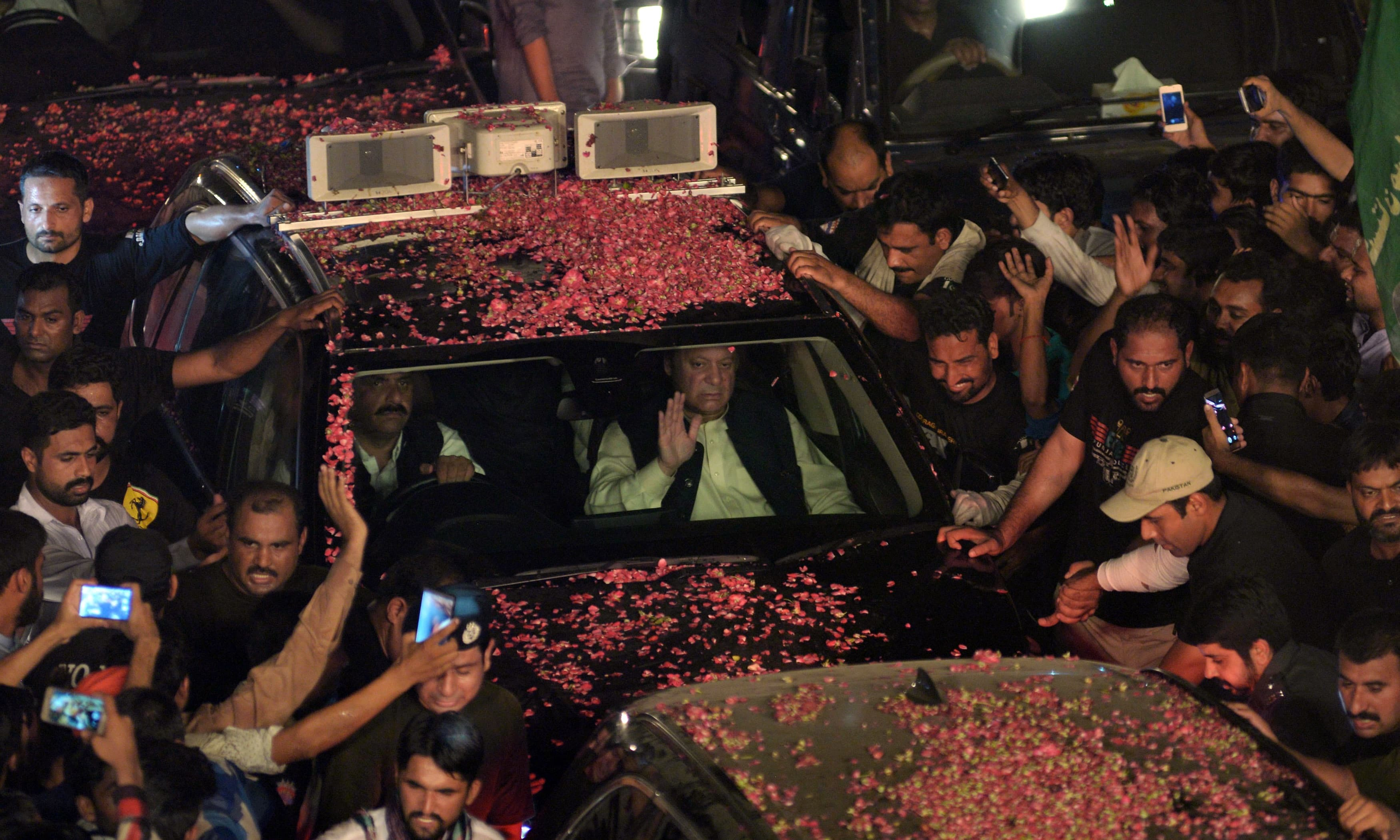 Pakistani ousted prime minister Nawaz Sharif (C) waves as his convoy passes supporters during a rally on August 12, 2017 in Lahore. Pakistan's former Prime Minister Nawaz Sharif's defiant procession down the ancient Grand Trunk Road after his ouster August 12 arrived in the outskirts of his eastern stronghold of Lahore as thousands rallied support. Photo:AFP