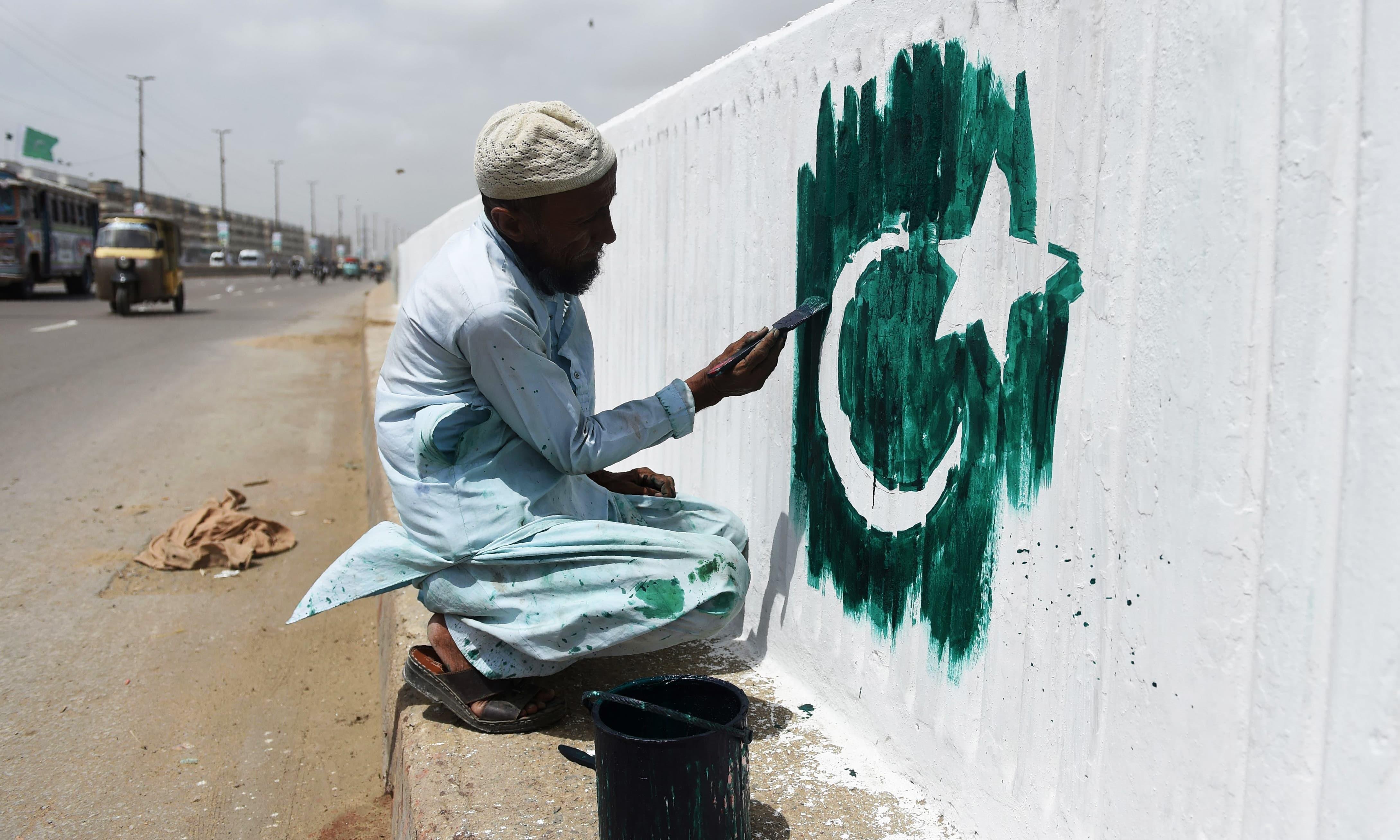 یوم آزادی سے قبل کراچی میں ایک شخص دیوار پر پاکستان کا پرچم پینٹ کر رہا ہے — فوٹو: اے ایف پی