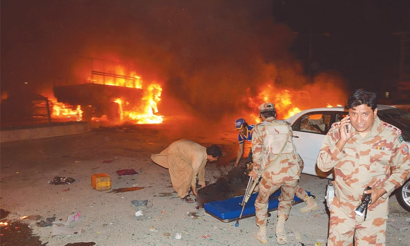 QUETTA: With some vehicles on fire, soldiers and volunteers remove a victim after a powerful bomb blast rocked the city on Saturday night.—AFP