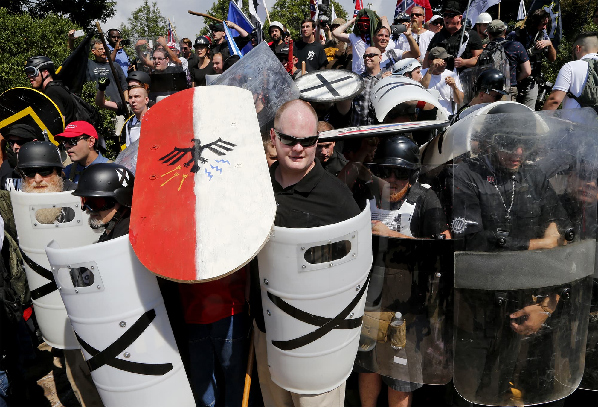 White supremacist demonstrators use shields as they guard the entrance to Lee Park in Charlottesville, VA. ─ AP