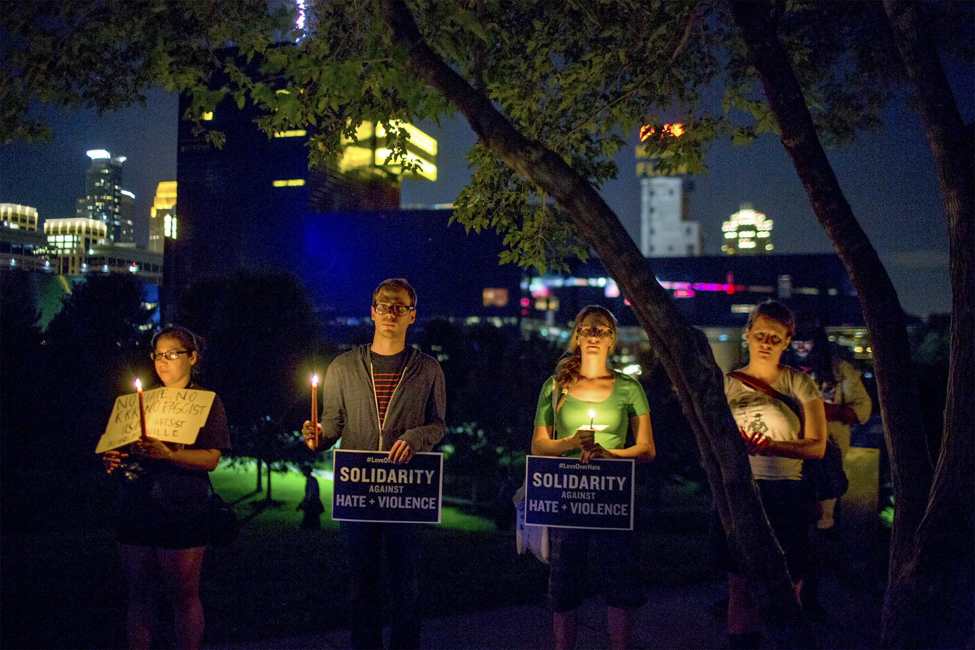 People stand atop a hill for a candlelight vigil in solidarity with Charlottesville, Virginia, counter-protesters at Gold Medal Park in Minneapolis. ─ AP