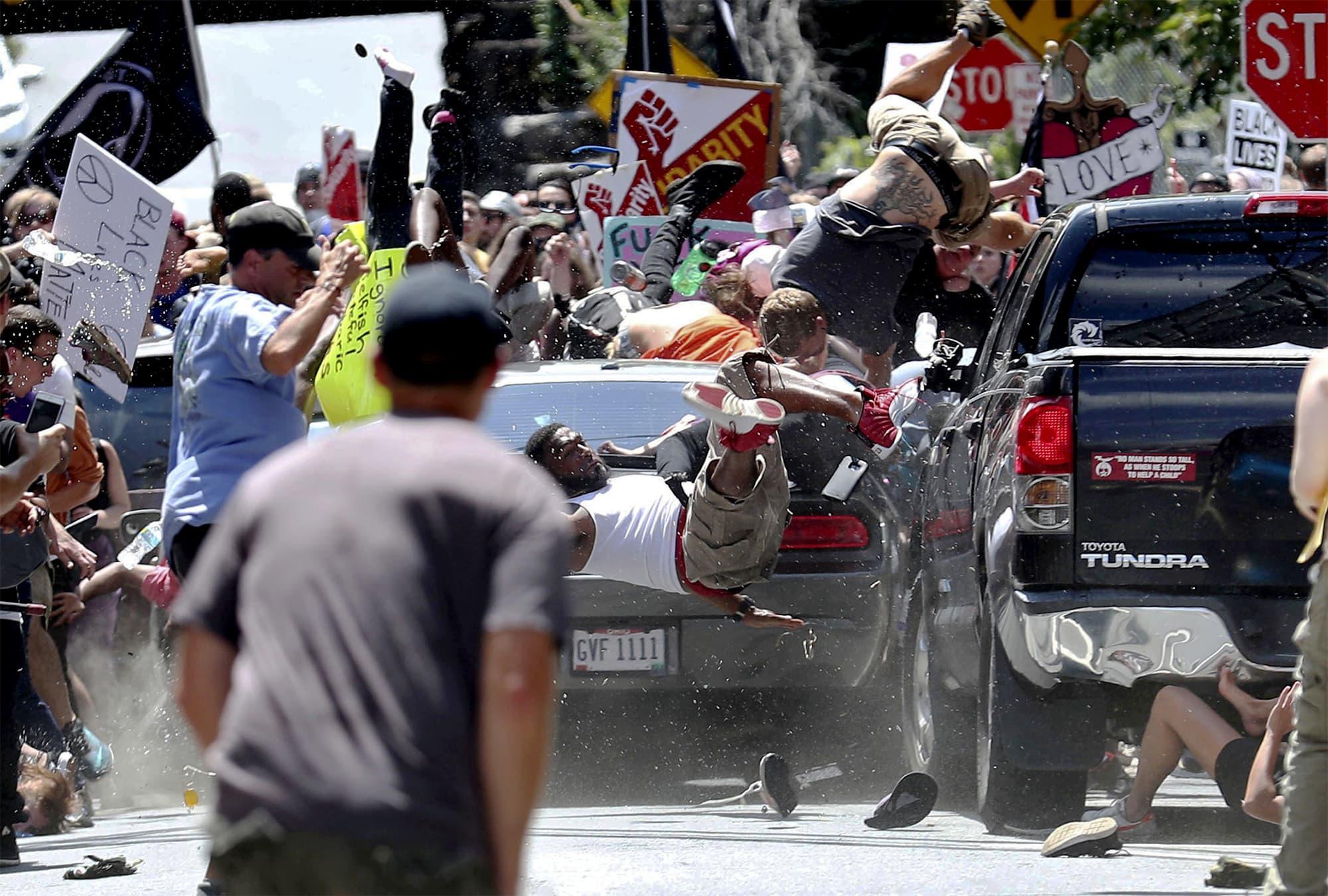 People fly into the air as a vehicle drives into a group of protesters demonstrating against a white supremacist rally in Charlottesville. ─ AP