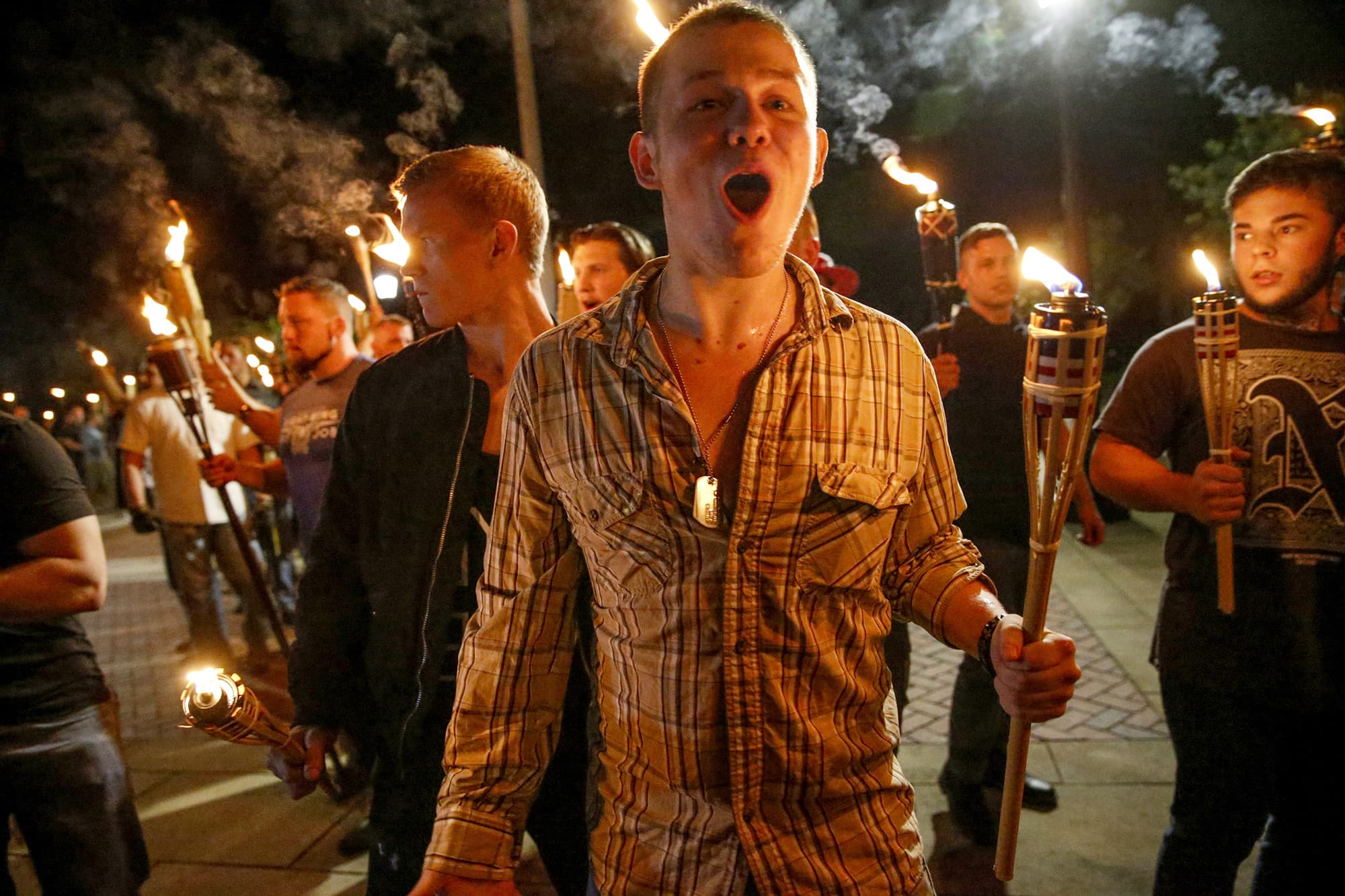 Multiple white supremacist groups march with torches through the UVA campus in Charlottesville. ─ AP