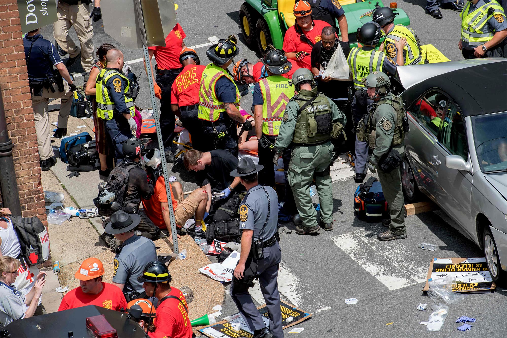 People receive first-aid after a car accident ran into a crowd of protesters in Charlottesville. ─ AFP