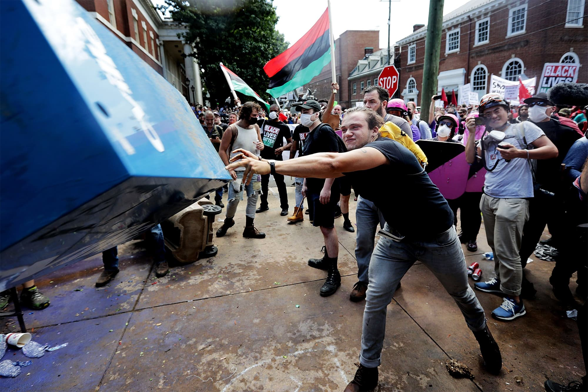 "An anti-fascist counter-protester hurls a newspaper box toward white supremacists, neo-Nazis and members of the ""alt-right"" during the ""Unite the Right"" rally outside Lee Park in Charlottesville. ─ AFP"