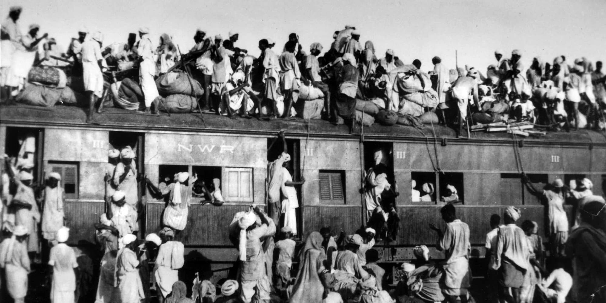 Muslim refugees sit on the roof of an overcrowded train near New Delhi as they try to flee India. AP Photo/File