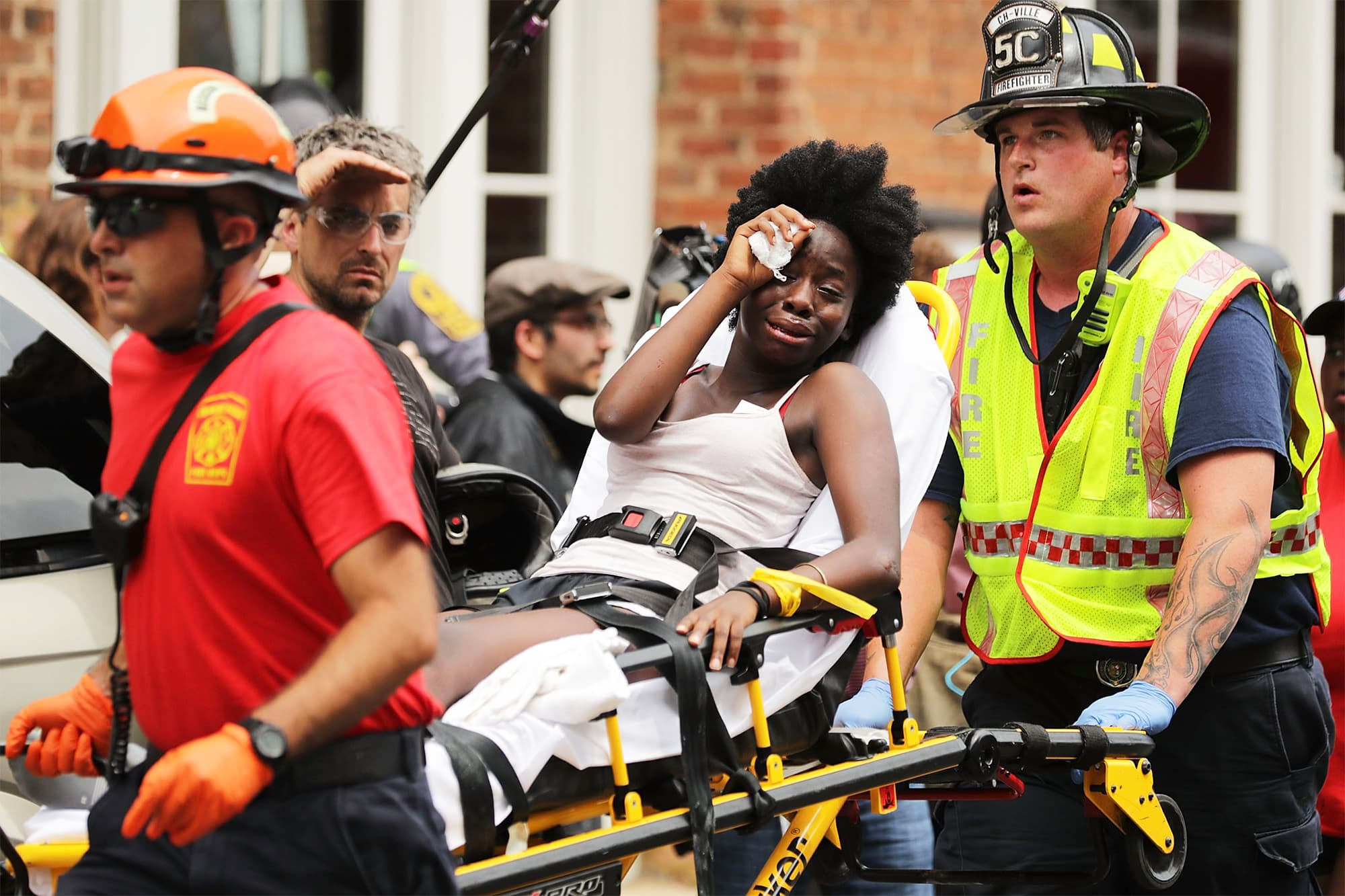 Rescue workers move victims on stretchers after car plowed through a crowd of counter-demonstrators marching through the downtown shopping district in Charlottesville. ─ AFP