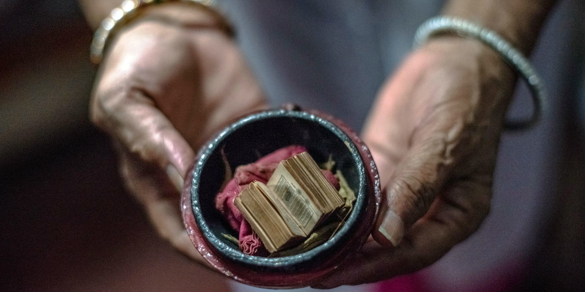 Shah Jahan Begum, 65, the wife of Indian Partition survivor Saleem Hasan Siddiqui, poses for a photograph with a miniature Koran his family saved during Partition. — AFP