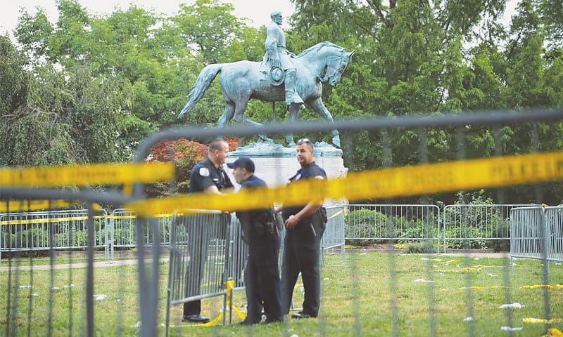 POLICEMEN guard the statue of Gen Robert E. Lee, which is at the centre of the controversy.—AFP