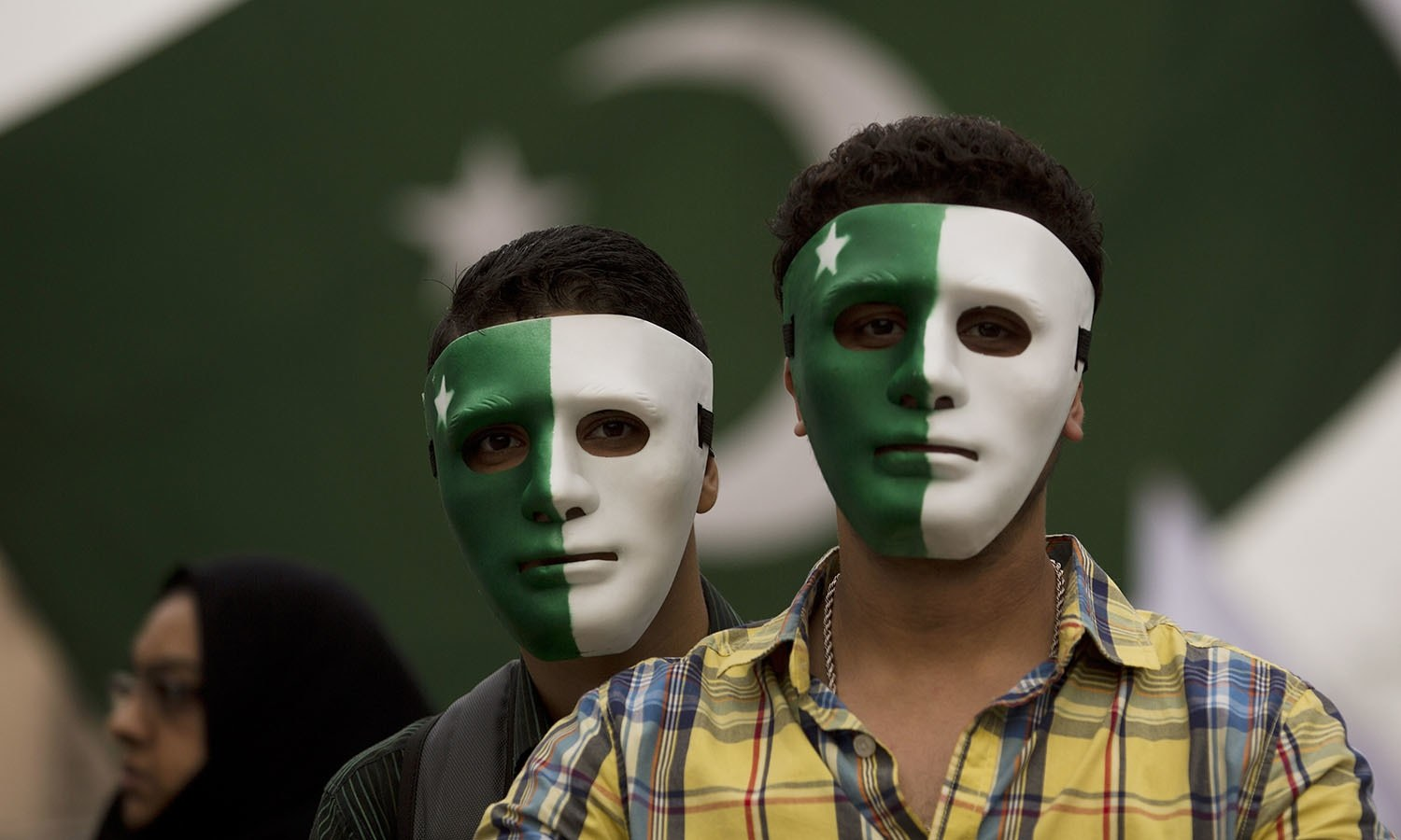 Youngsters wear masks painted in the design of the national flag to celebrate the country's 69th Independence Day in Rawalpindi.— AP/File