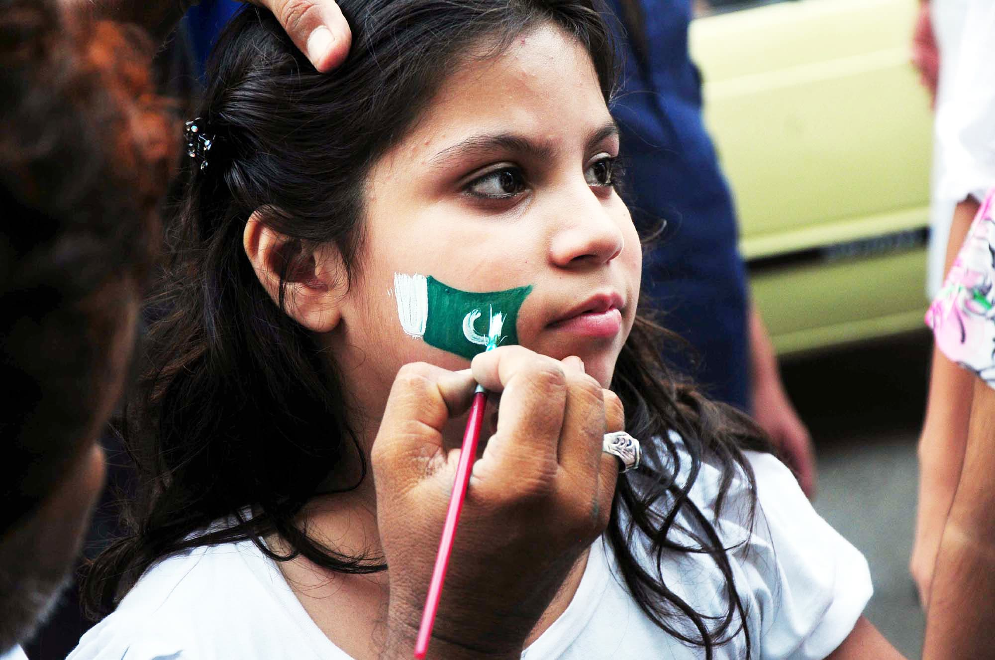 Girl gets the national flag painted on her cheek. — AFP