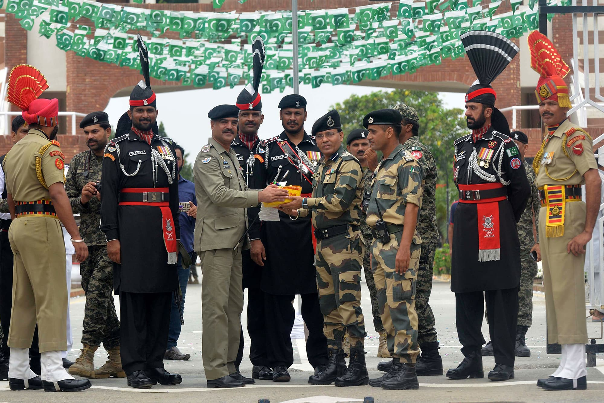 Pakistani Wing Commander Bilal (4L) presents sweets to Indian Border Security Force (BSF) Commandant Sudeep (4R) during a ceremony to celebrate Independence Day at the Wagah border post. — AFP