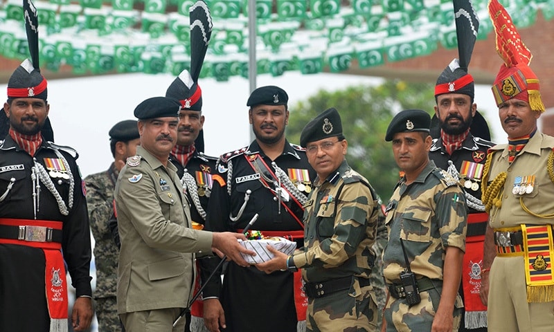 Pakistani Wing Commander Bilal (2L) presents sweets to Indian Border Security Force Commandant Sudeep (4R).— AFP