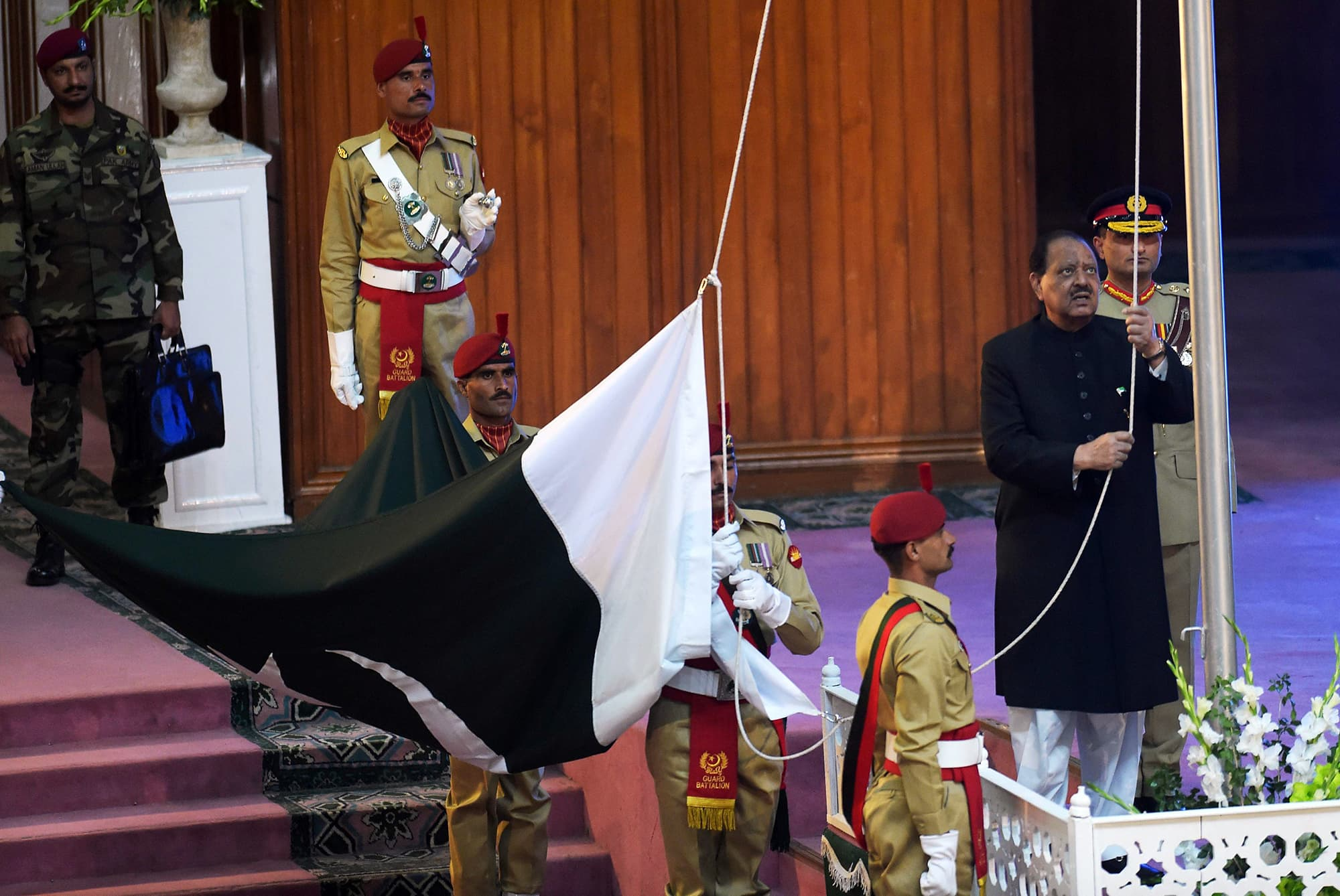 President Mamnoon Hussain hoists the national flag during a ceremony to mark Independence Day in Islamabad. — AFP