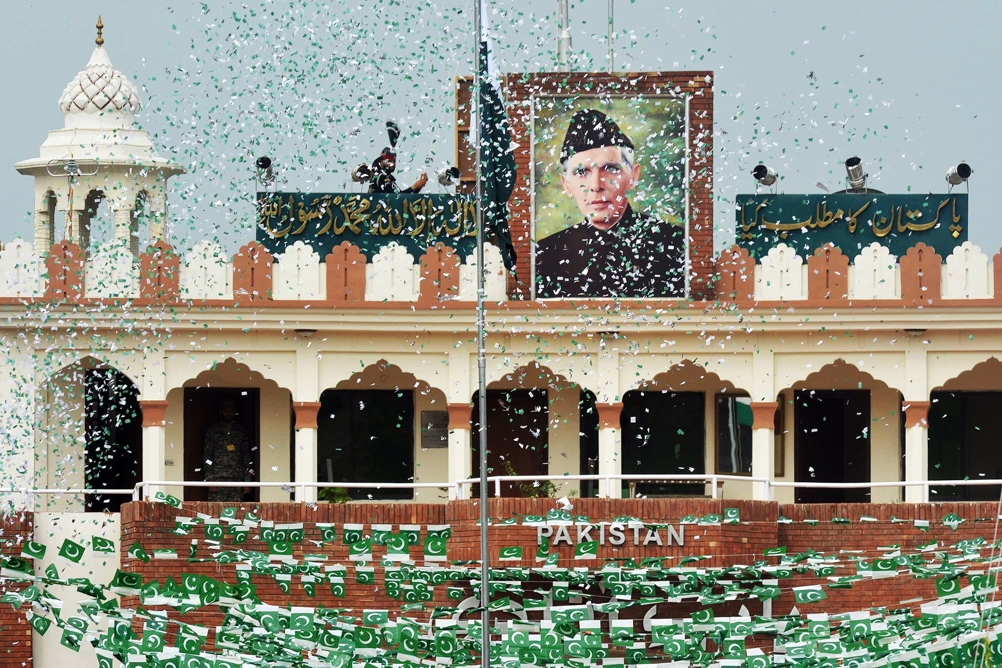 The portrait of Muhammad Ali Jinnah is seen at at the India-Pakistan Wagah border post as a Pakistani Ranger (top) unfurls the Pakistani national flag during a ceremony to celebrate Pakistan's Independence Day. — AFP