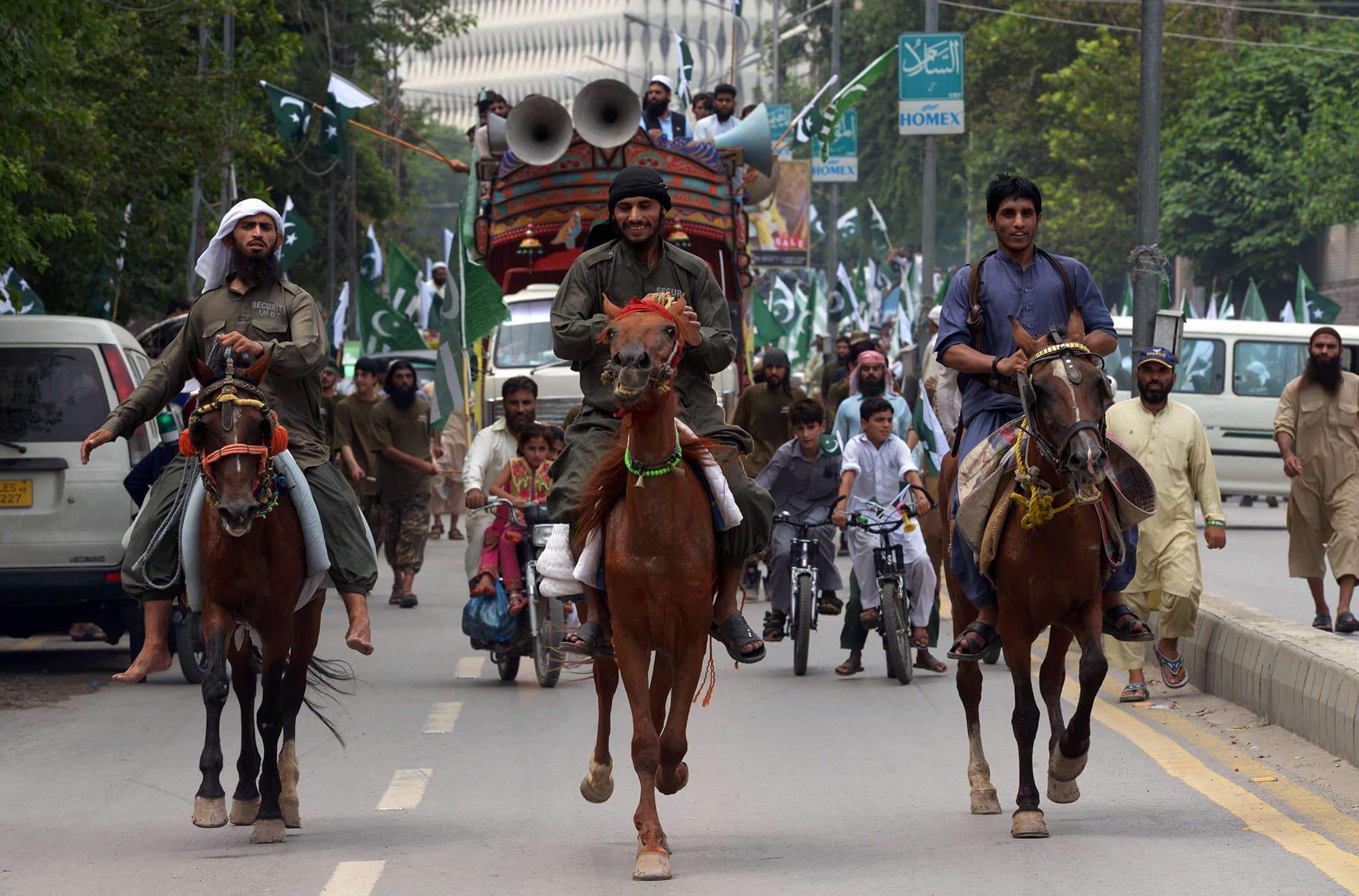 People march on horses during a rally marking the country's Independence Day in Peshawar. — AFP
