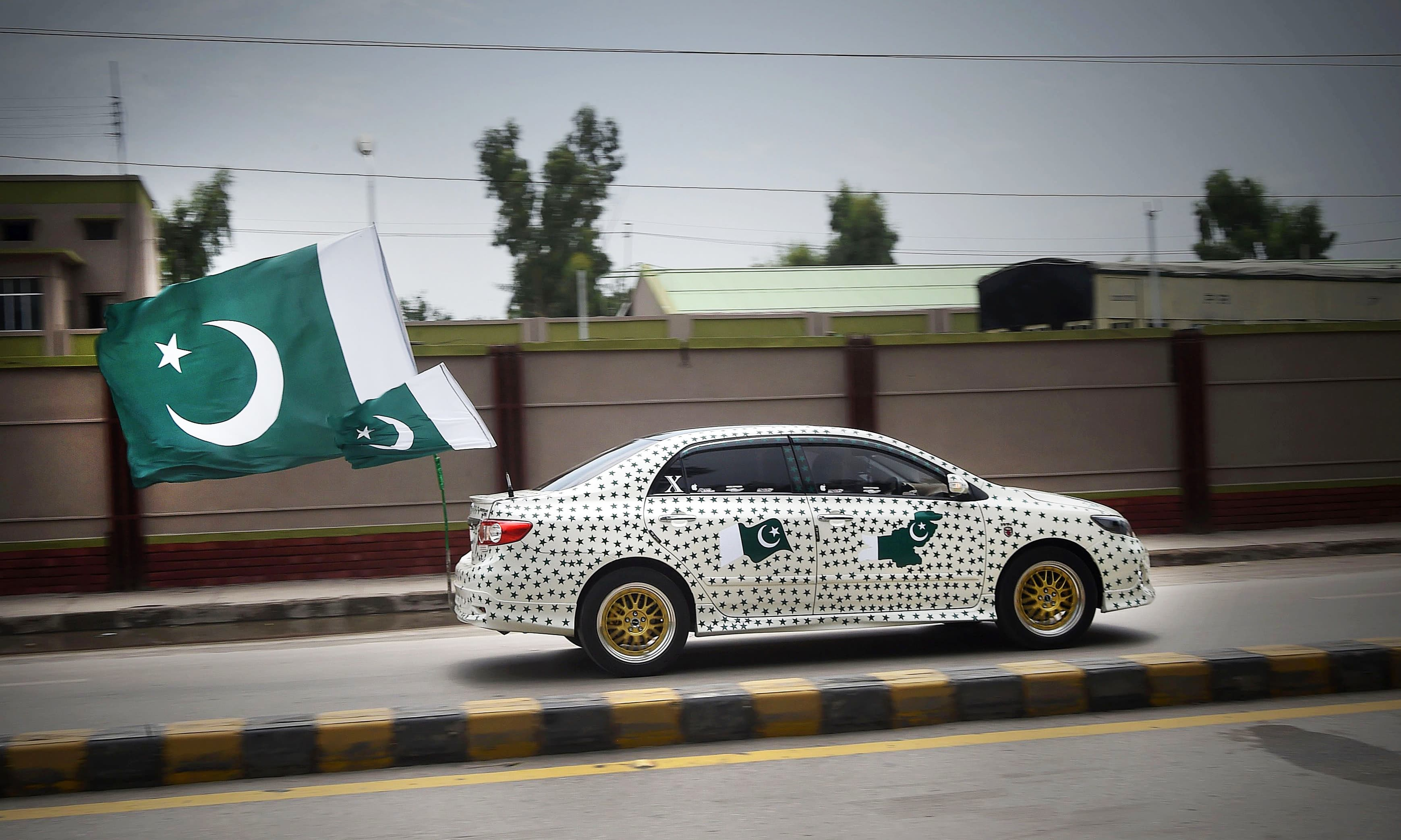 A resident drives his car decorated with national flags to mark Independence Day in Peshawar on August 14. —AFP