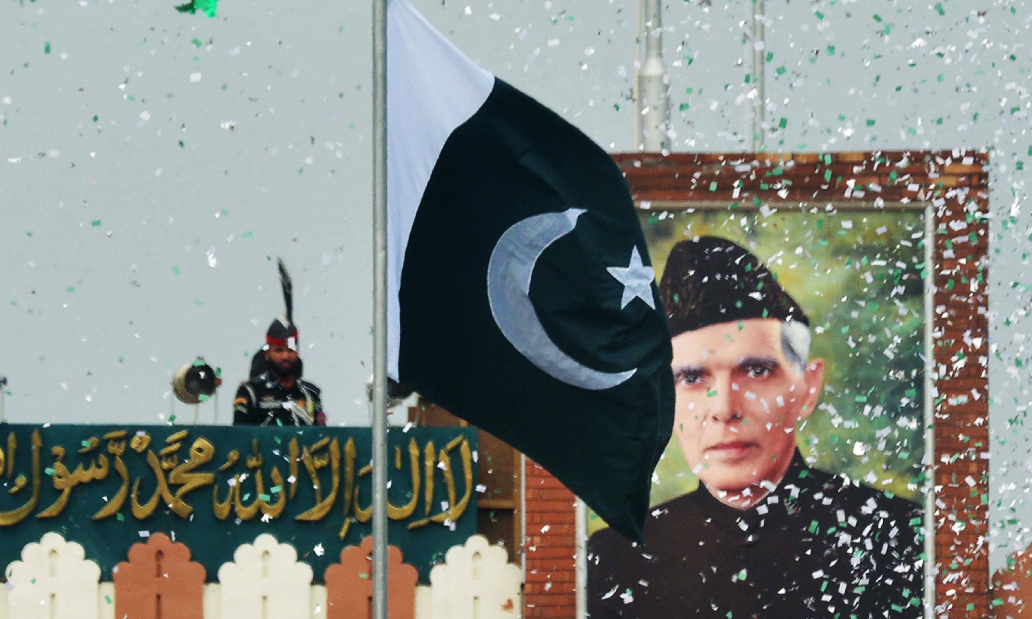 The portrait of Muhammad Ali Jinnah is seen at at the Wagah border post as a Pakistani Ranger (top) unfurls the Pakistani national flag during a ceremony to celebrate Independence Day. —AFP