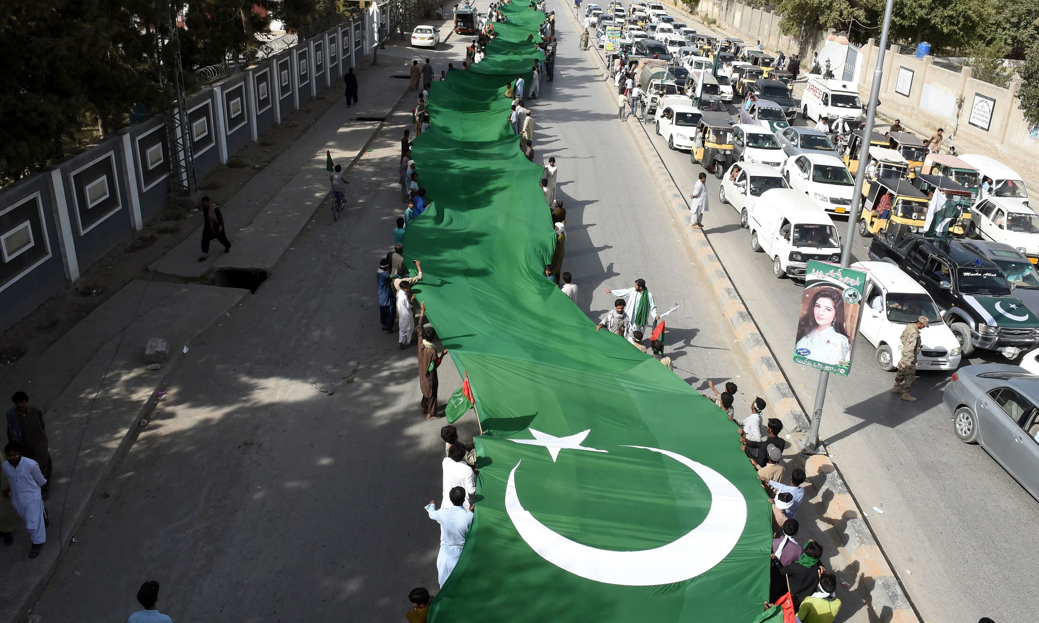 Residents carry a huge flag during a rally in Quetta. —AFP