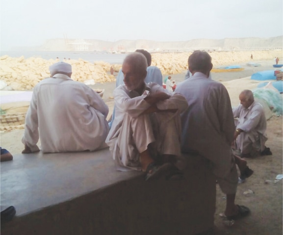 A GROUP of fishermen at Komari Ward of Mulla Band, where they gather to chat or play ludo.—Photo by writer