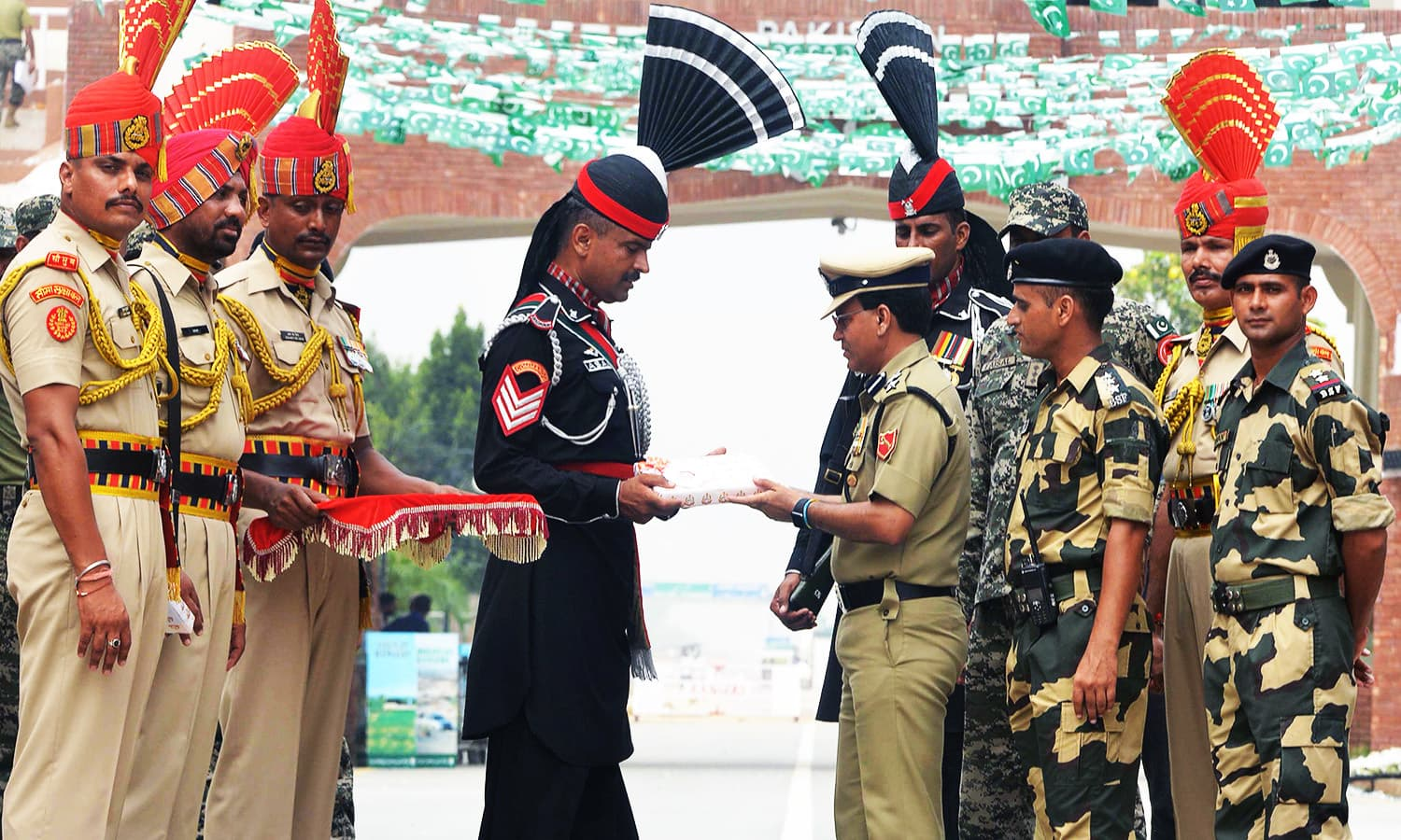 Indian BSF Commandant Sudeep presents sweets to Pakistani Wing Commander Bilal. —AFP