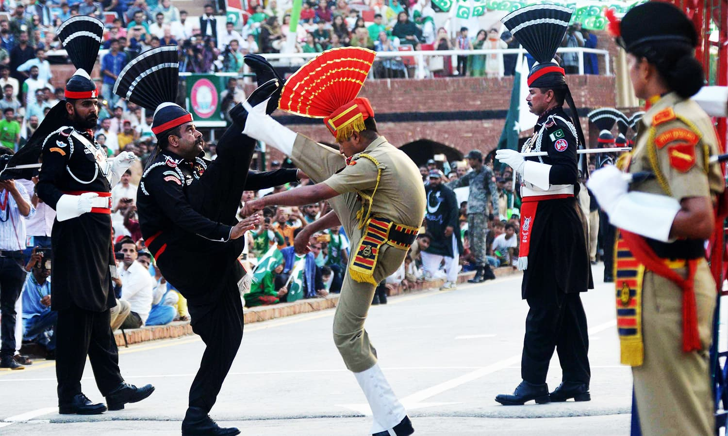 Pakistani Rangers and Indian Border Security Force personnel perform during the daily beating of the retreat ceremony at the India-Pakistan Wagah Border Post.—AFP