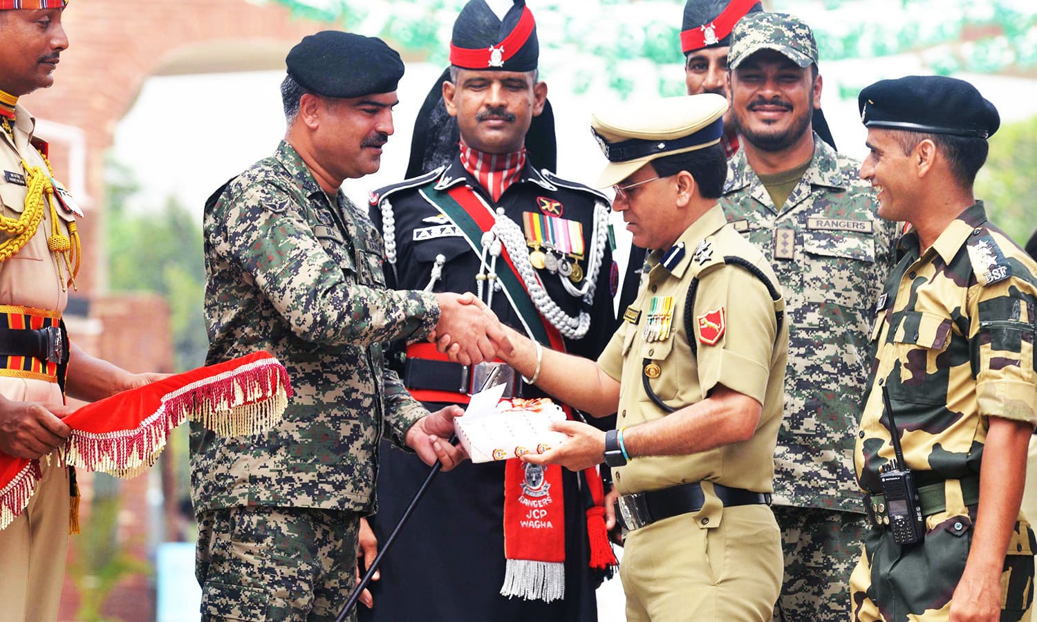 Indian BSF Commandant Sudeep presents sweets as he shakes hand with the Pakistani Wing Commander Bilal during a ceremony at the India-Pakistan Wagah border post.—AFP