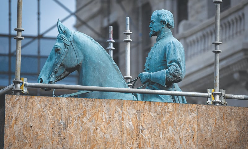 (Top) A Sheriff stands near the toppled statue of a Confederate soldier in front of the old County Courthouse in Durham, North Carolina. (Below left) A monument to Confederate General John Hunt Morgan stands encased in a protective scaffolding outside the Historic Lexington Courthouse in Lexington, Kentucky. (Below right) Protesters gather below a vandalised monument dedicated to Confederate Major John B. Castleman while demanding that it be removed from the public square in Louisville, Kentucky.—Agencies