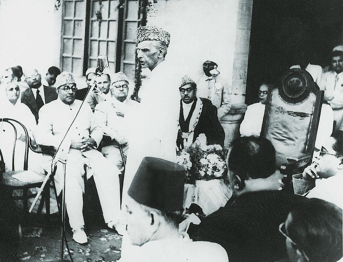 Quaid-i-Azam Mohammad Ali Jinnah speaks at a civic reception held in his honour by the Karachi Municipal Corporation (KMC) at the KMC headquarters on August 25, 1947. Mayor Hakeem Muhammad Ahsan is seen on the right, while Nawabzada Liaquat Ali Khan and Sir Ghulam Hussain Hidayatullah are on the left. —​ Dawn/White Star Archives