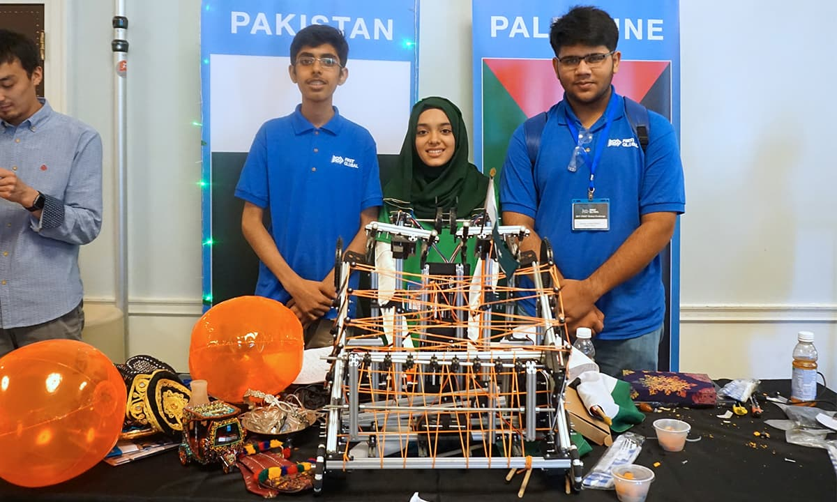 Waheed, Kiyani, and Bhatti stand before their robot at the 2017 FIRST Global challenge | Photo by Ritu Prasad, Medill News Service