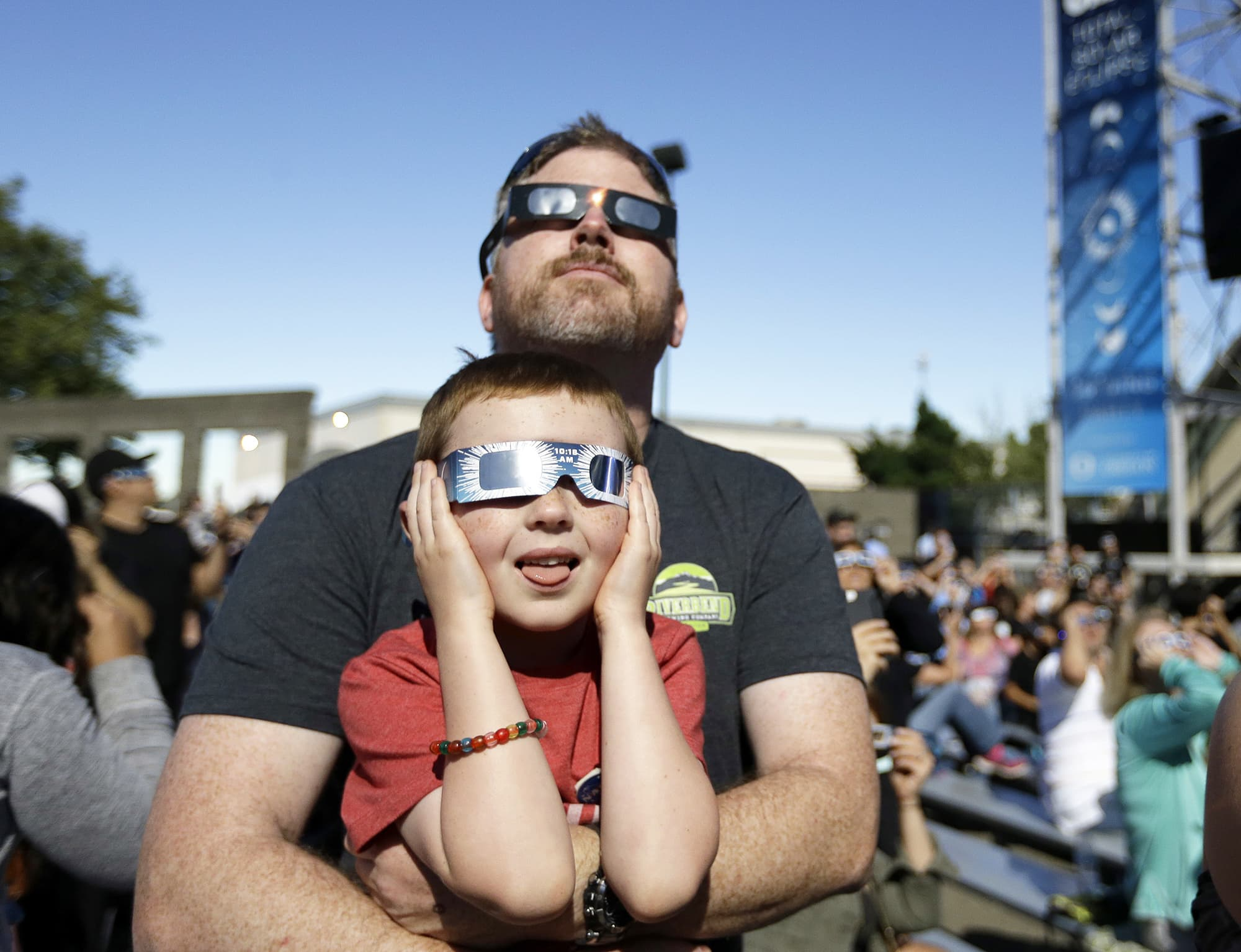 Dan Blanchette and his son, Sam, 6, watch the final phases of a total solar eclipse in Salem, Oregon, USA.—AP