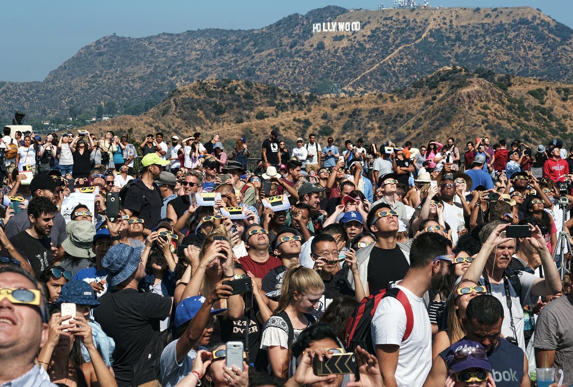 A crowd gathers in front of the Hollywood sign at the Griffith Observatory to watch the solar eclipse in Los Angeles. — AP