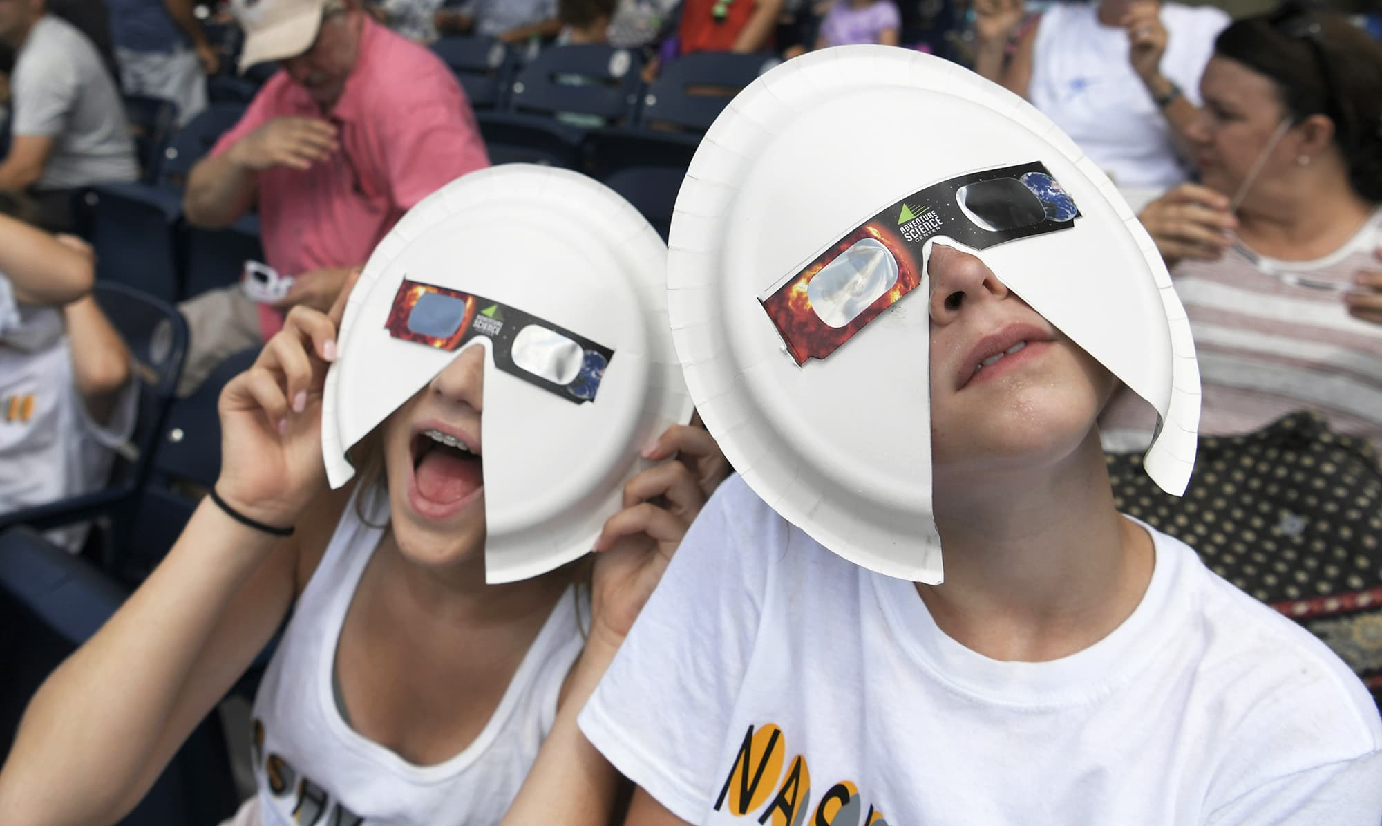 Annie Gray Penuel and Lauren Peck, both of Dallas, wear their makeshift eclipse glasses at Nashville's eclipse viewing party ahead of the solar eclipse at First Tennessee Park.— AP