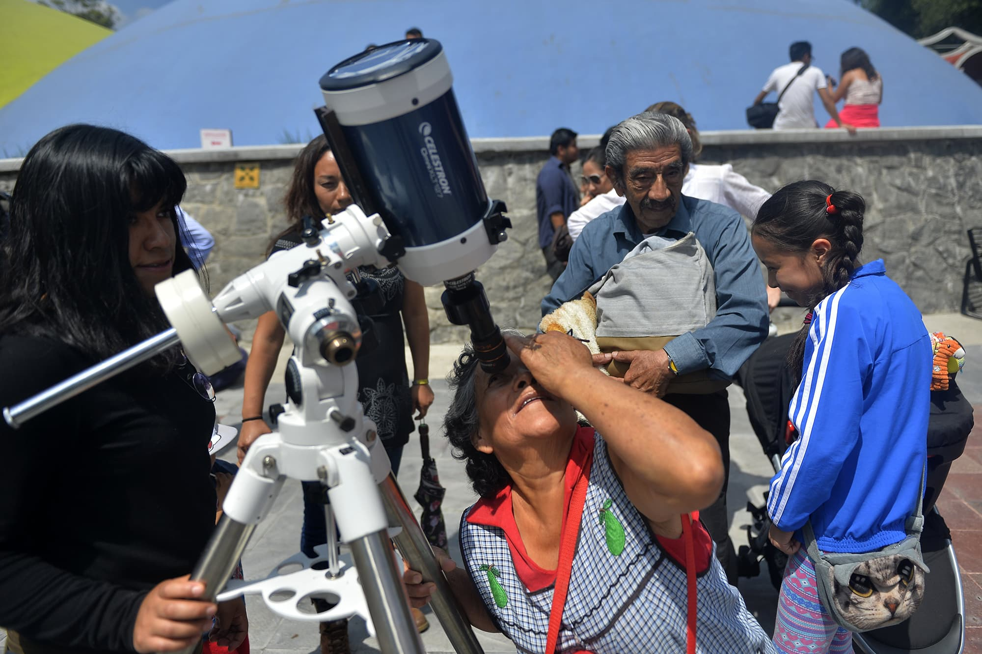 A Mexican woman looks through a telescope at the beginning of the solar eclipse, at the esplanade of the Museum of Natural History in Mexico City, Mexico.—AFP