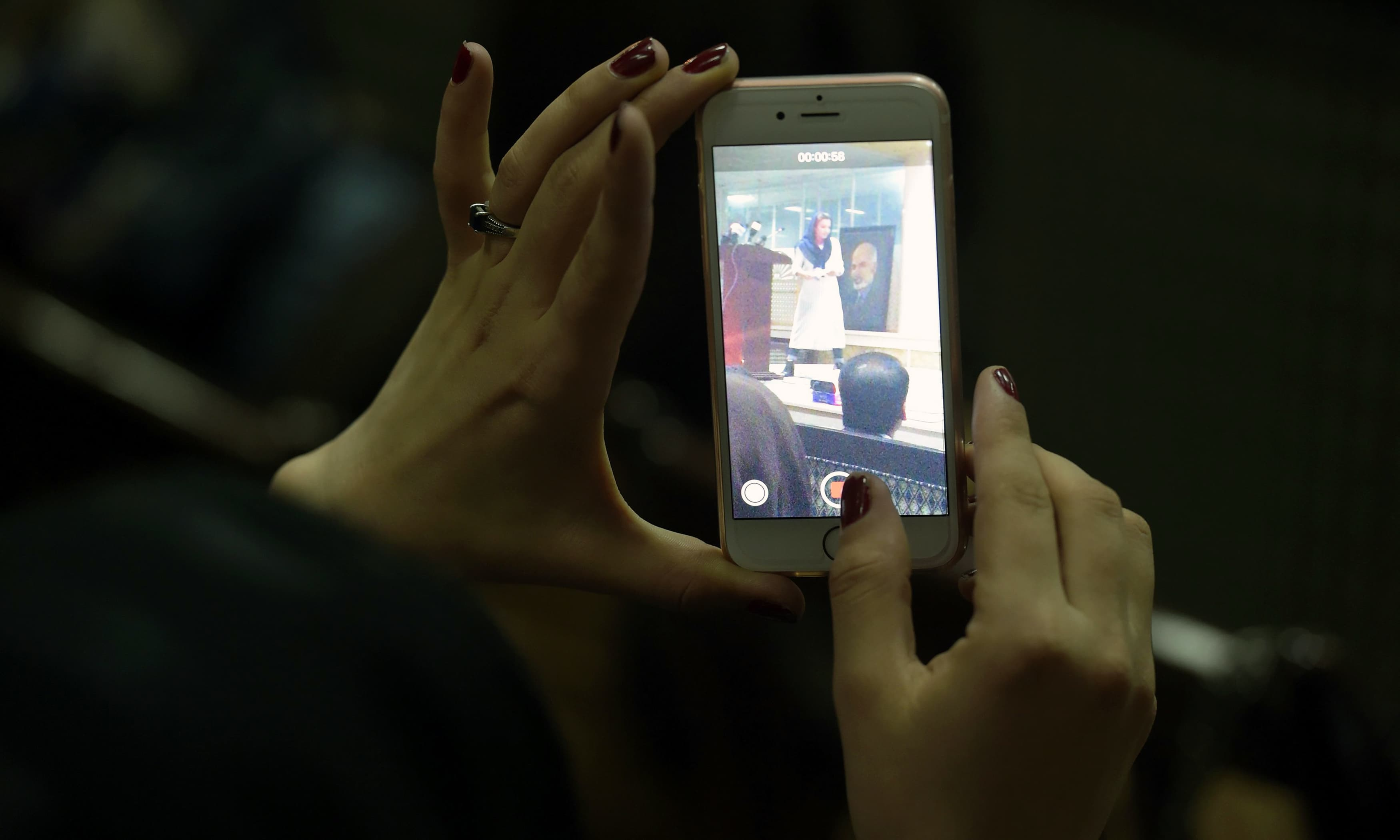 A woman records footage on her mobile phone at the event.—AFP