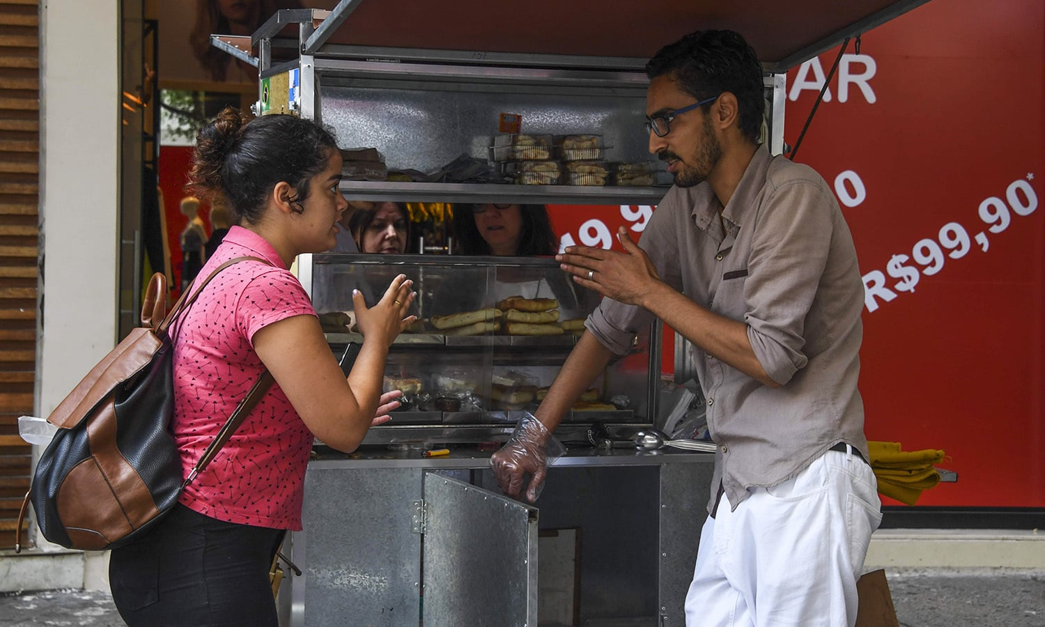 Mohamed Ali Abdelmoatty Kenawy attends to a customer at his food stand.— AFP