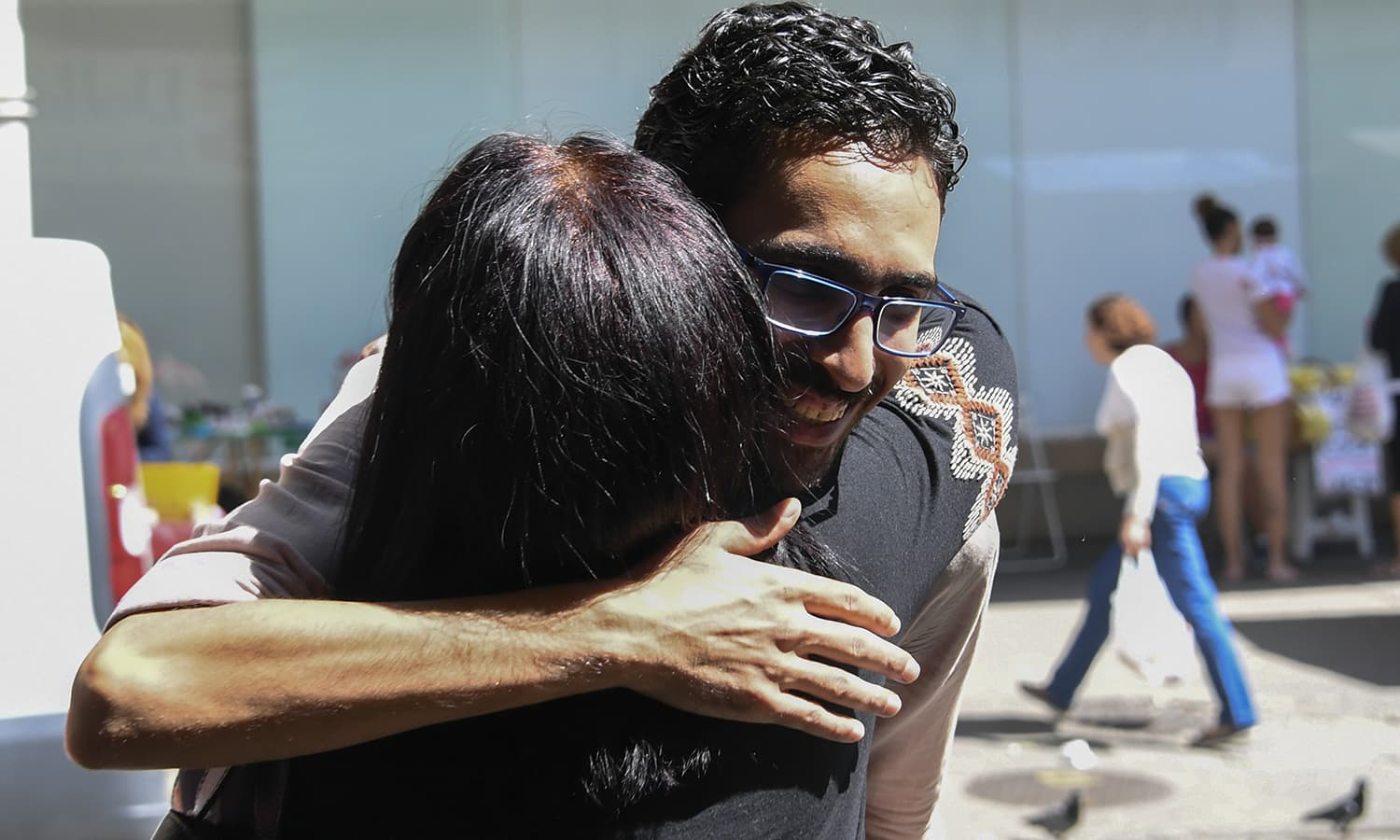 """Egyptian immigrant Mohamed Ali Abdelmoatty Kenawy, who was attacked three weeks ago by four men screaming """"Go back to your country!"""", hugs a customer at his food stand in the Copacabana neighbourhood in Rio de Janeiro on August 24.— AFP"""