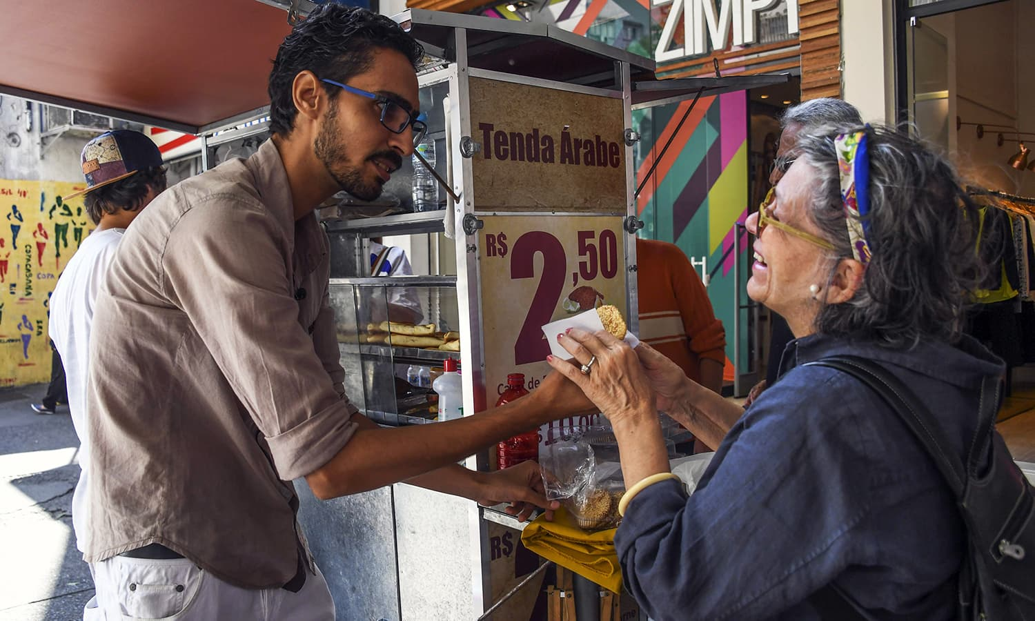 Mohamed Ali Abdelmoatty Kenawy attends to a customer at his food stand in Rio de Janeiro.— AFP