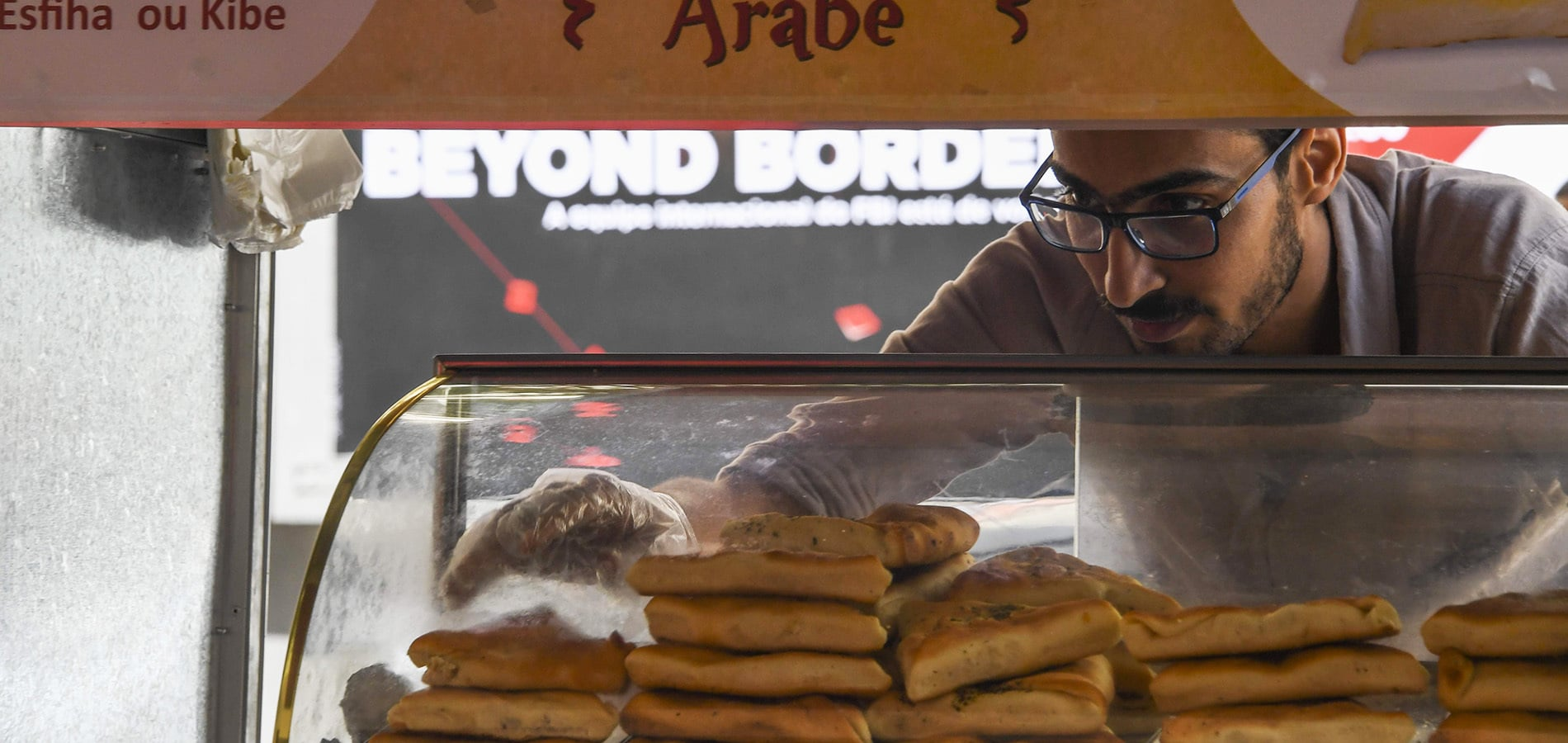 Egyptian immigrant Mohamed Ali Abdelmoatty Kenawy works at his food stand in the Copacabana neighborhood in Rio de Janeiro.-AFP