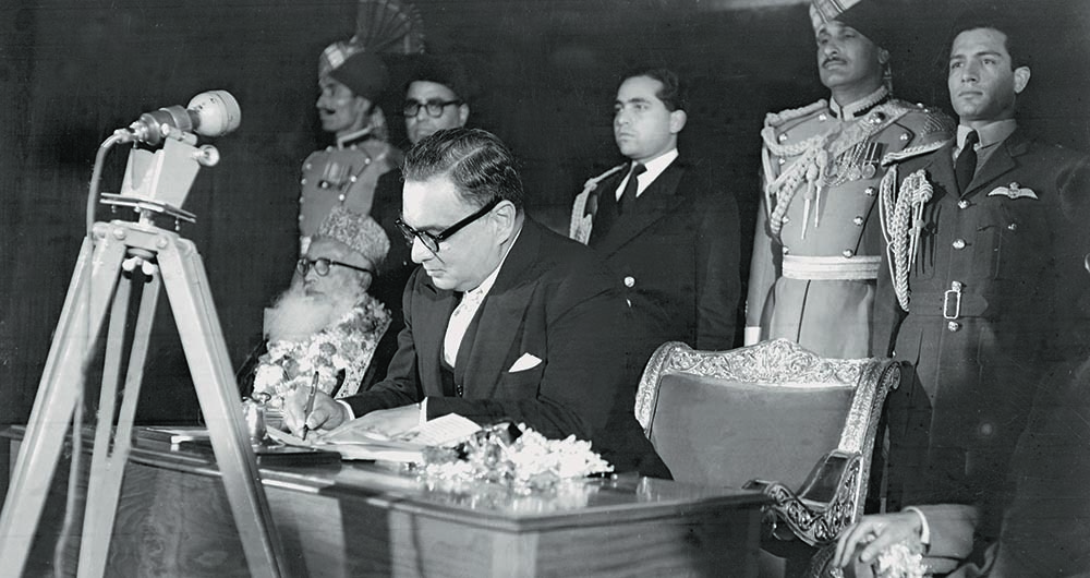 Governor General Iskander Mirza signing his assent on the 1956 Constitution Bill at a ceremony held on March 2, 1956, in Karachi. The Constitution takes effect from March 23, 1956, and marks the country's transition from a British Dominion to a full-fledged Republic. — The Press Information Department, Ministry of Information, Broadcasting & National Heritage, Islamabad