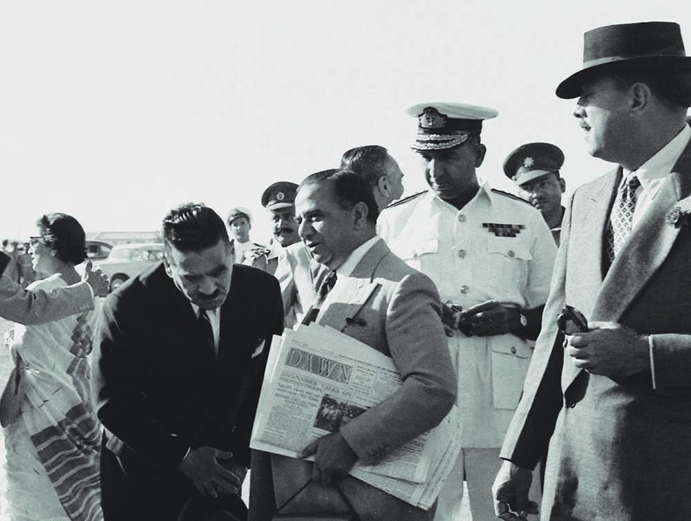 Huseyn Shaheed Suhrawardy, the country's fourth prime minister, with a copy of Dawn under his arm, departs from Karachi on an official visit to Iraq, Turkey and Saudi Arabia. General Ayub Khan, Commander in Chief of Pakistan Army, is seen on the extreme right gazing at the prime minister. —The Press Information Department, Ministry of Information, Broadcasting & National Heritage, Islamabad
