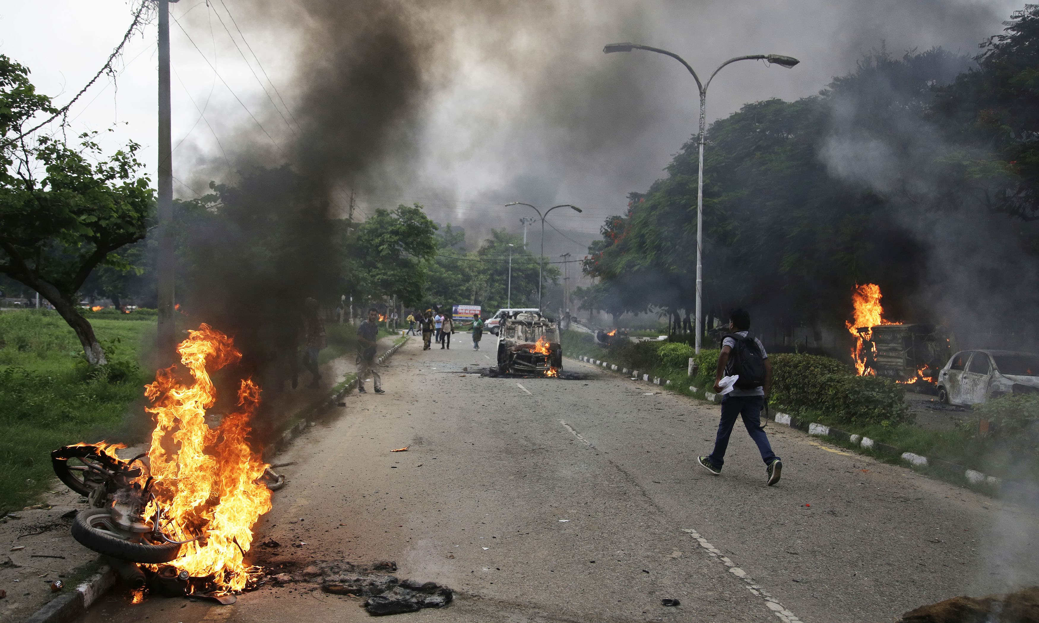 Vehicles set alight by Dera Sacha Sauda sect members burn in the streets of in Panchkula, India, Friday, Aug 25. —AP