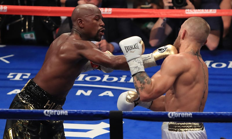 Floyd Mayweather Jr. throws a punch at Conor McGregor during their super welterweight boxing match.─AFP
