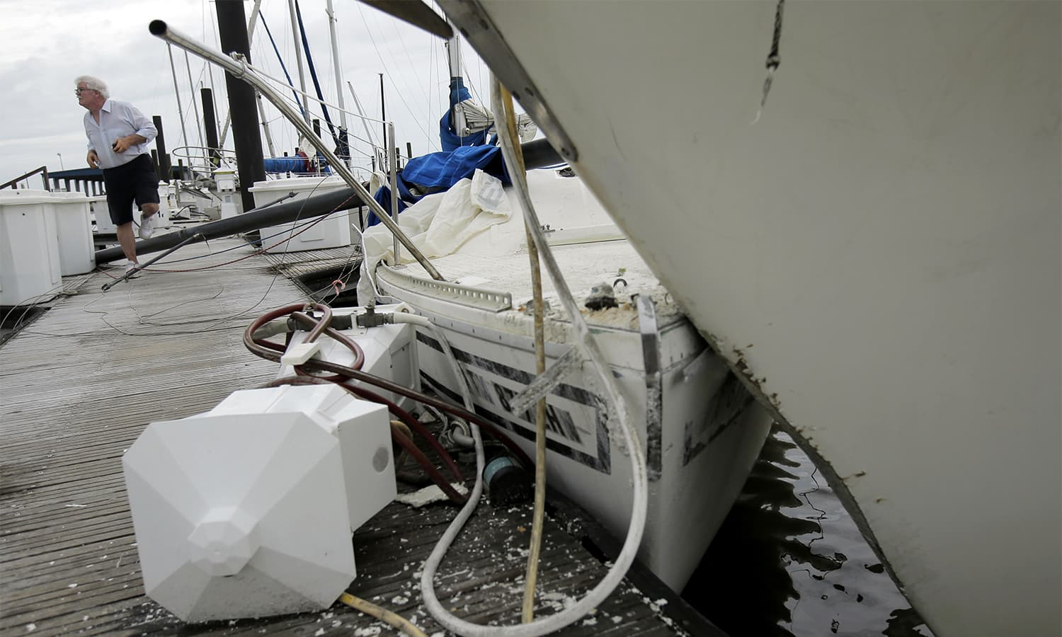 A resident looks at boats damaged by Hurricane Harvey. — AP