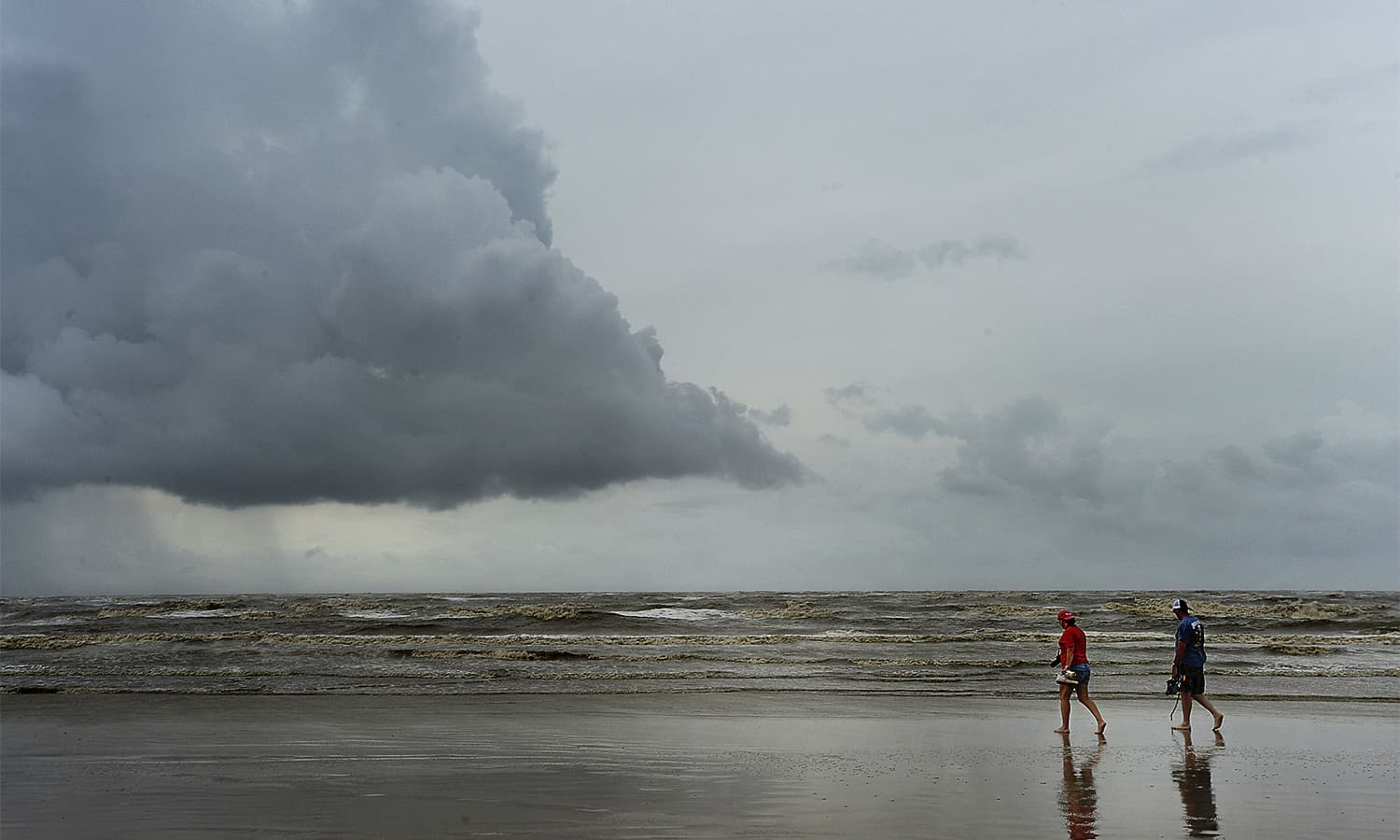 A couple strolls along the shore in McFaddin Beach, Texas as storm clouds build on the horizon the day after Hurricane Harvey made land, battering the gulf communities near Corpus Christi. — AP