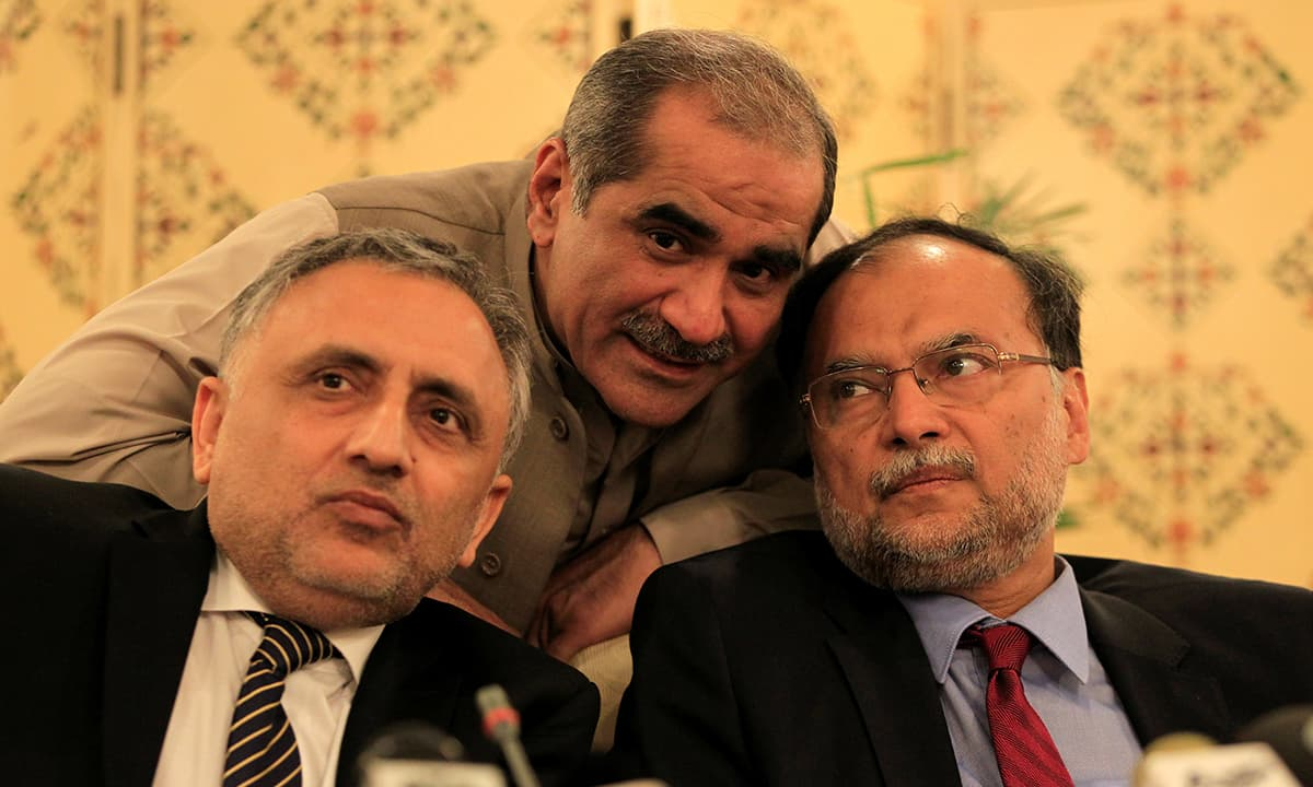 PMLN leaders Khawaja Saad Rafique, Ahsan Iqbal and Zafarullah Khan huddle before the start of a news conference | Reuters