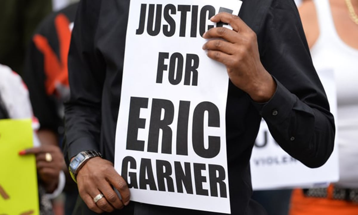 A man holds a placard at a memorial for Eric Garner in Staten Island | AFP