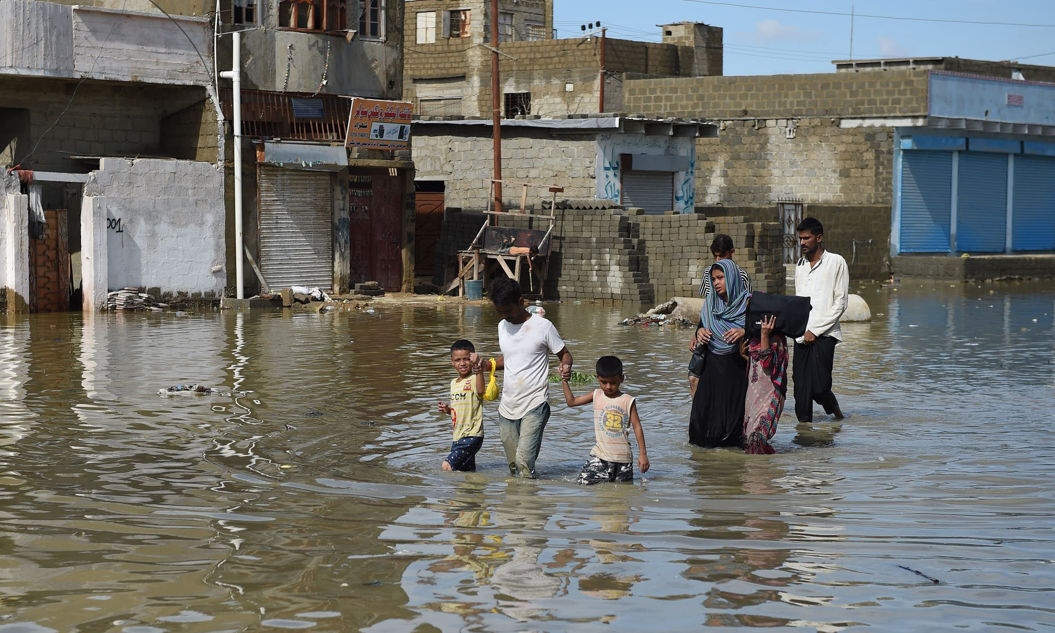 A family makes their way on a flooded street after heavy rain in Karachi on August 31, 2017. ─ AFP